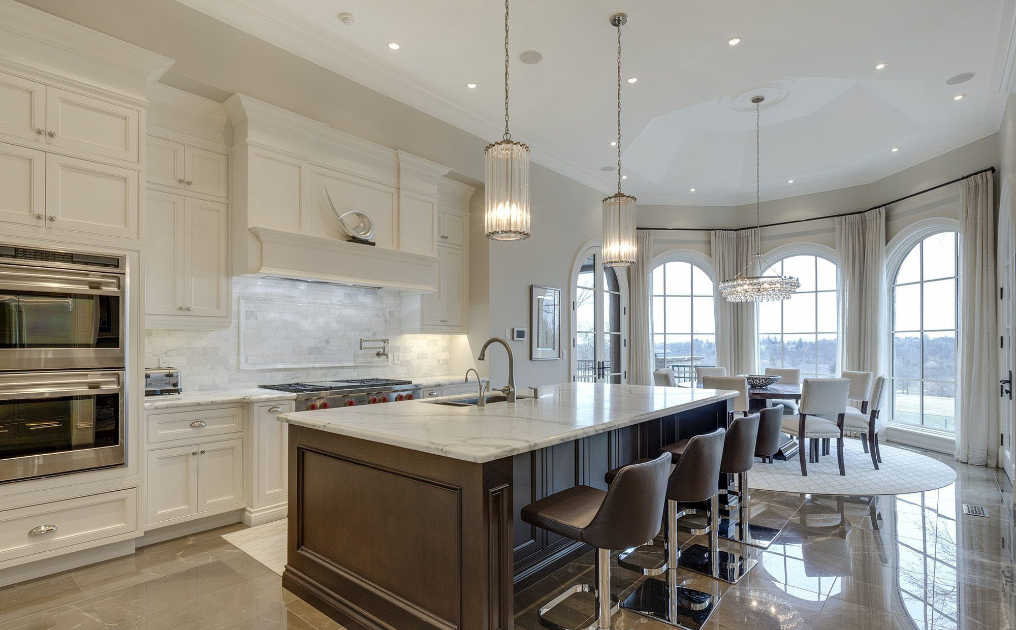 Beautiful luxury kitchen featuring cream colored cabinets, marble counter and backsplash with a deep brown island.