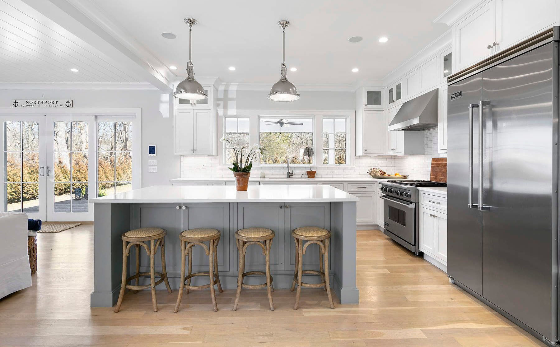 White and gray multi color kitchen cabinets with white quartz counters, white subway tile backsplash and pale wood floors.