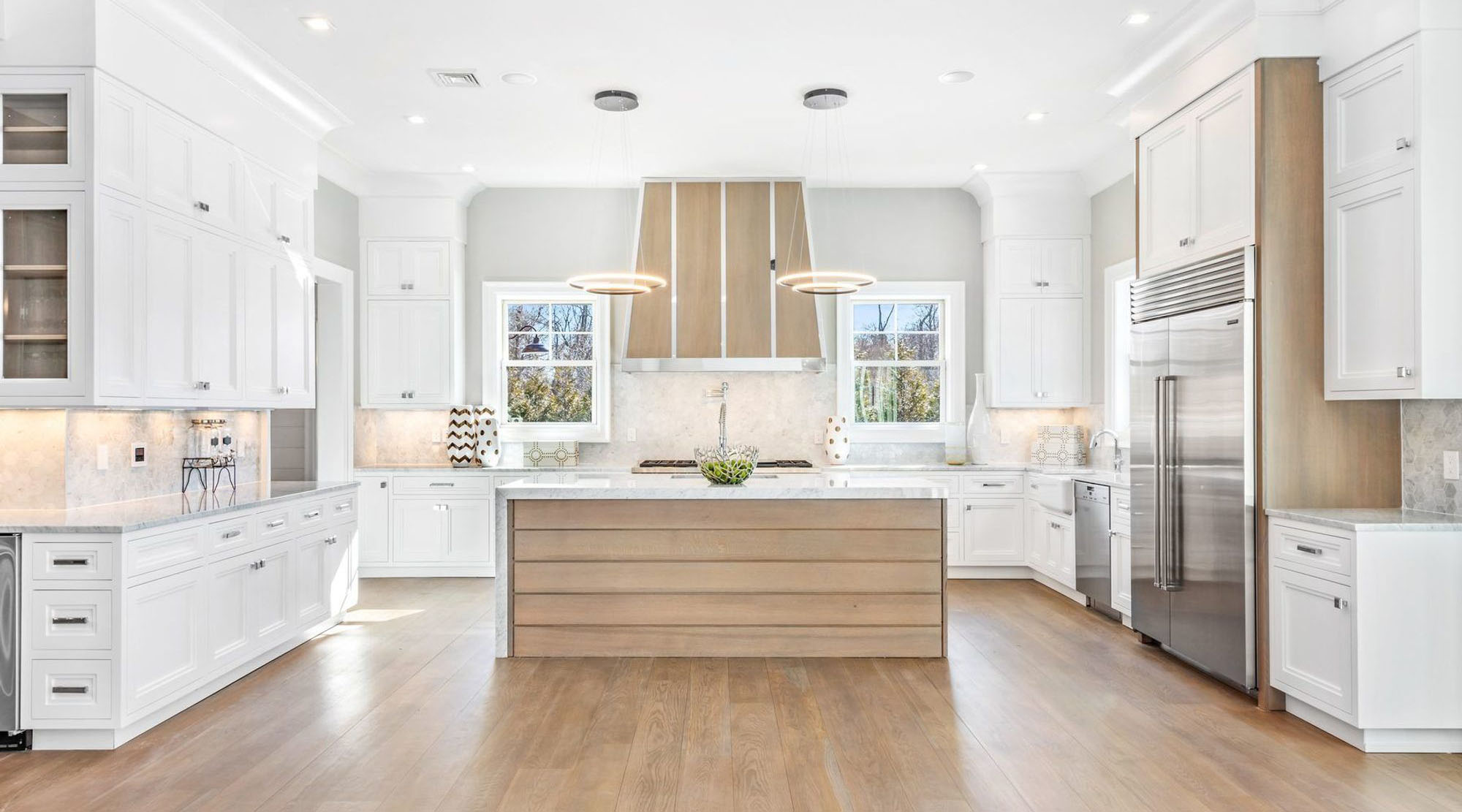 White cabinets with a light wood shiplap style island.