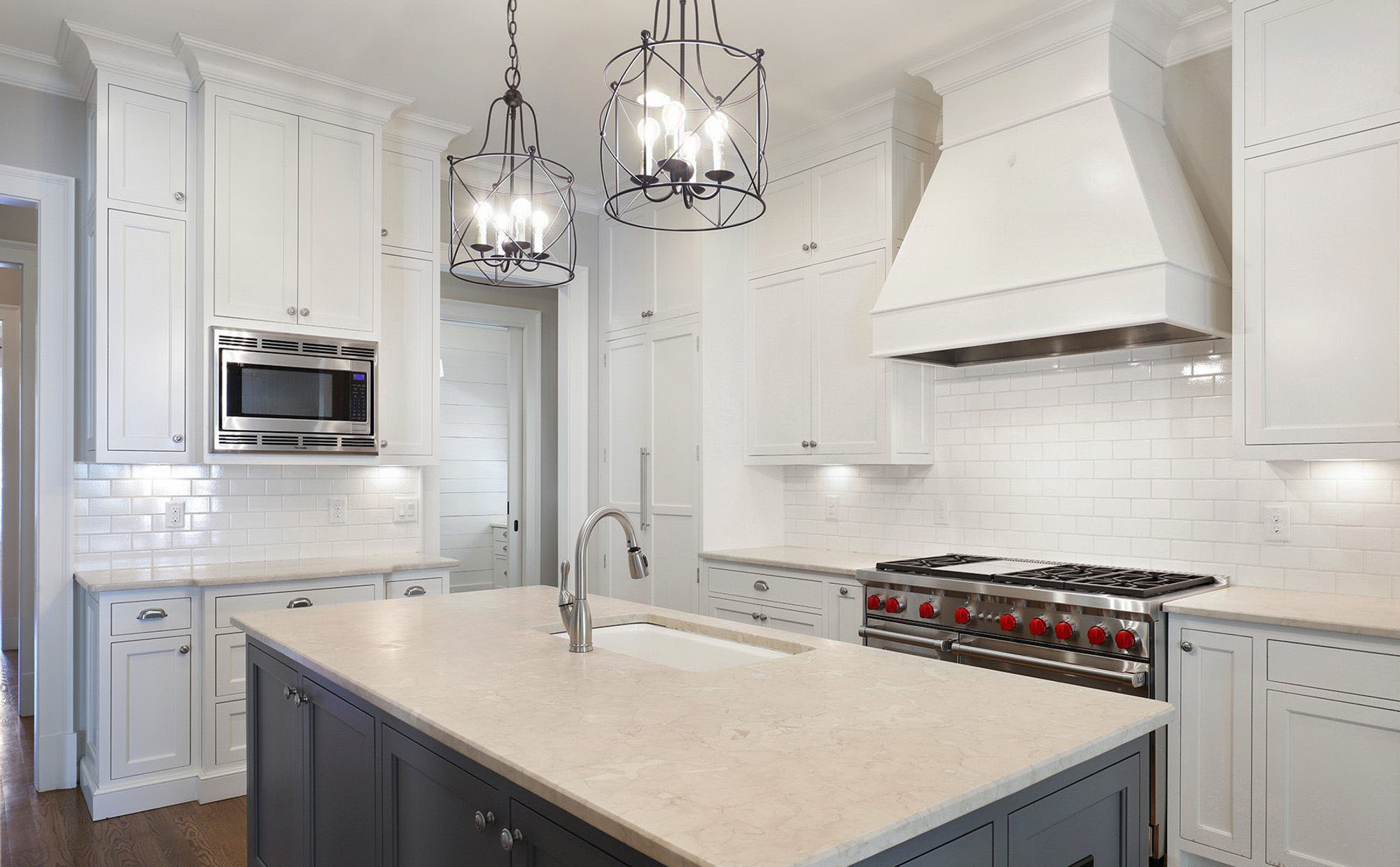 This medium gray island is a nice choice along side the white shaker style cabinetry. two tone kitchen cabinets.