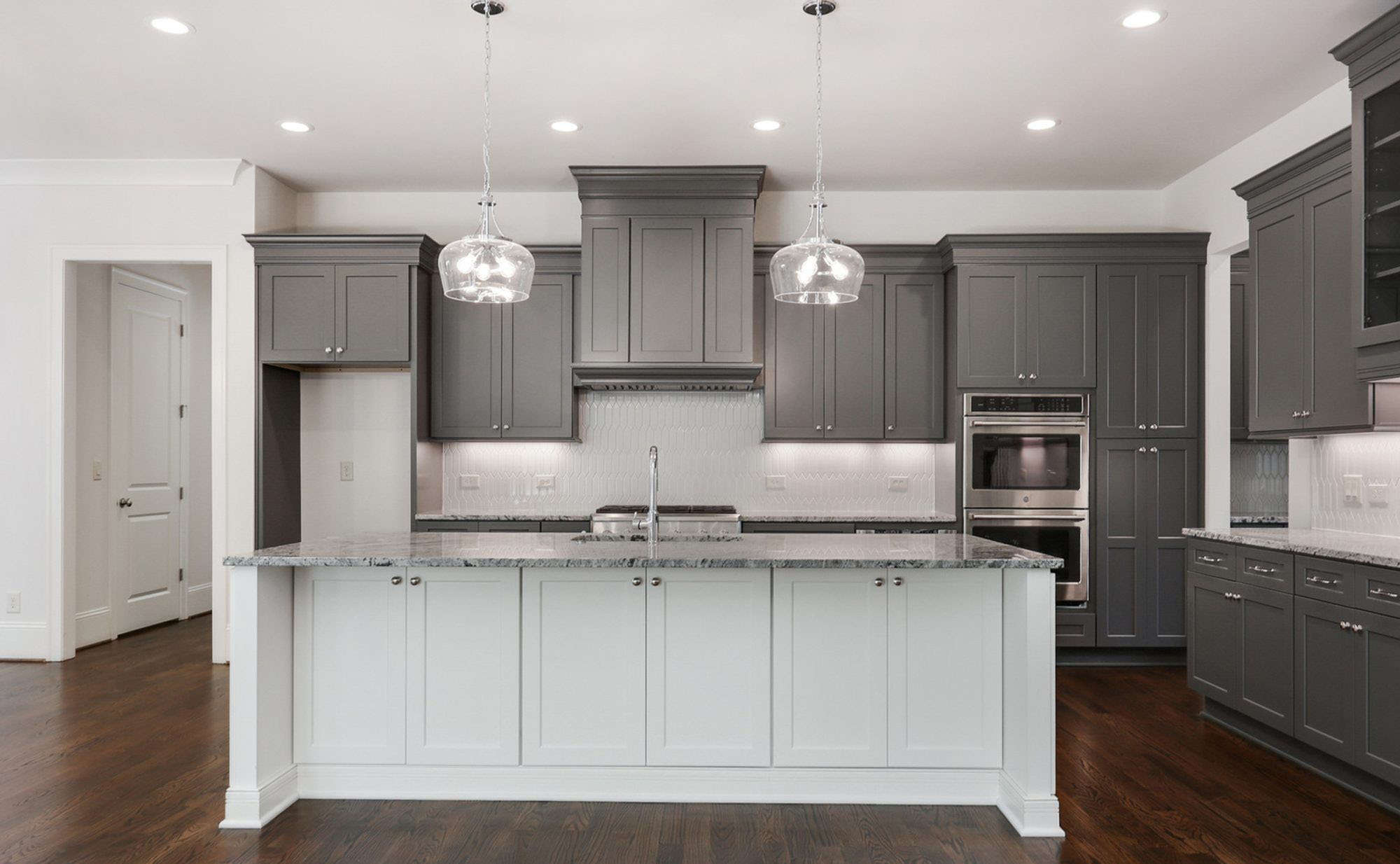 medium gray shaker style cabinets with a white island. Dark brown hardwood floors.