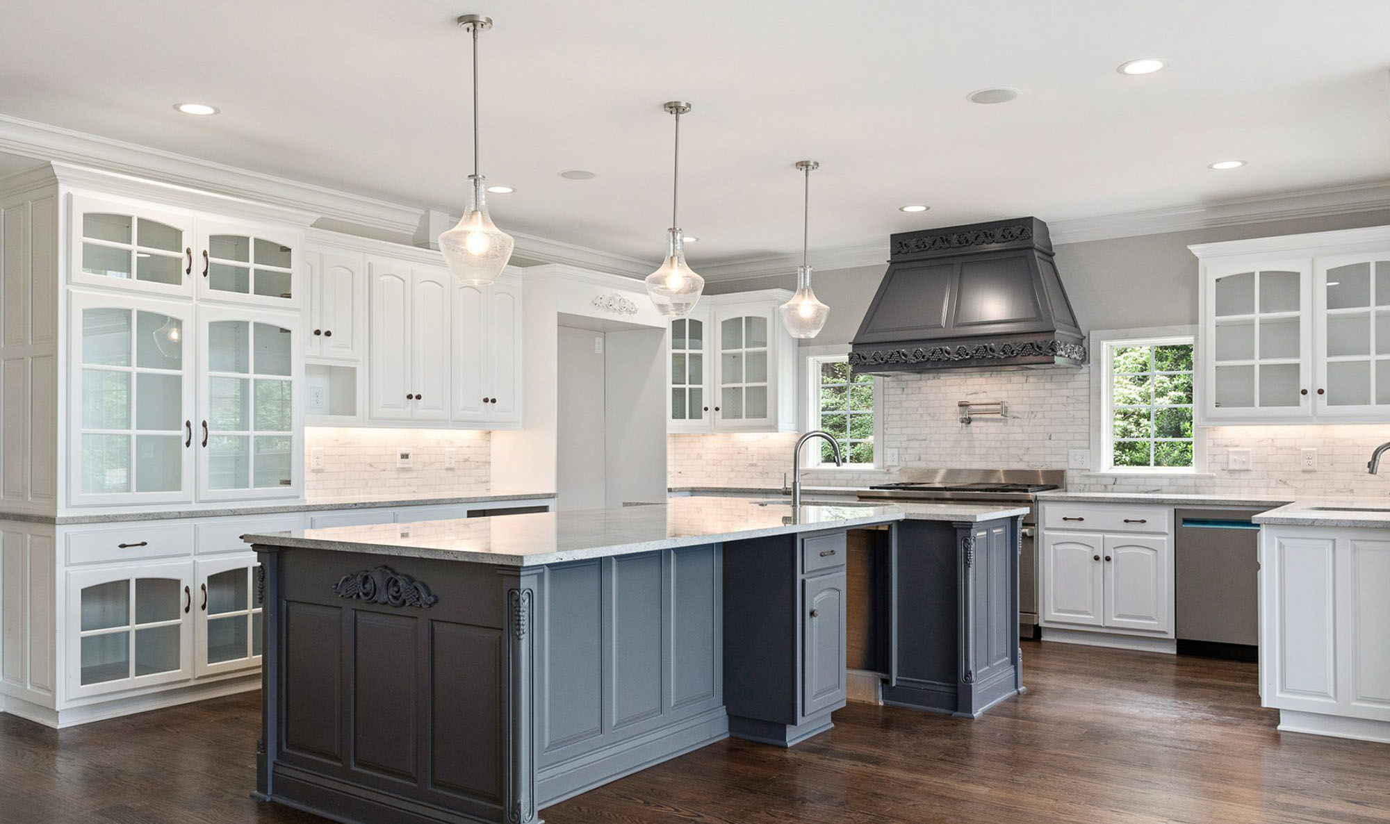 Country style white and gray kitchen with white cabinetry and dark gray island. Marble countertops with matching backsplash. medium brown wood floors.