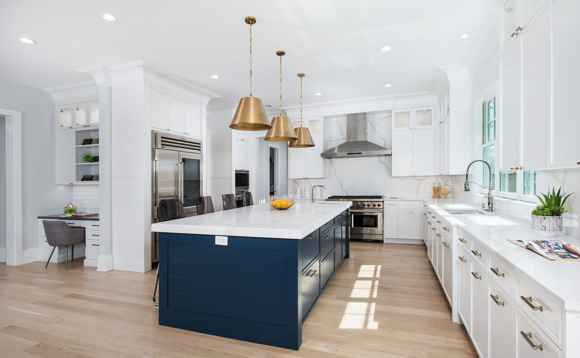 Multi color kitchen cabinets featuring a combination of white cabinets with a deep blue island. Pale hardwood floors, gold hardware and stainless steel appliances.