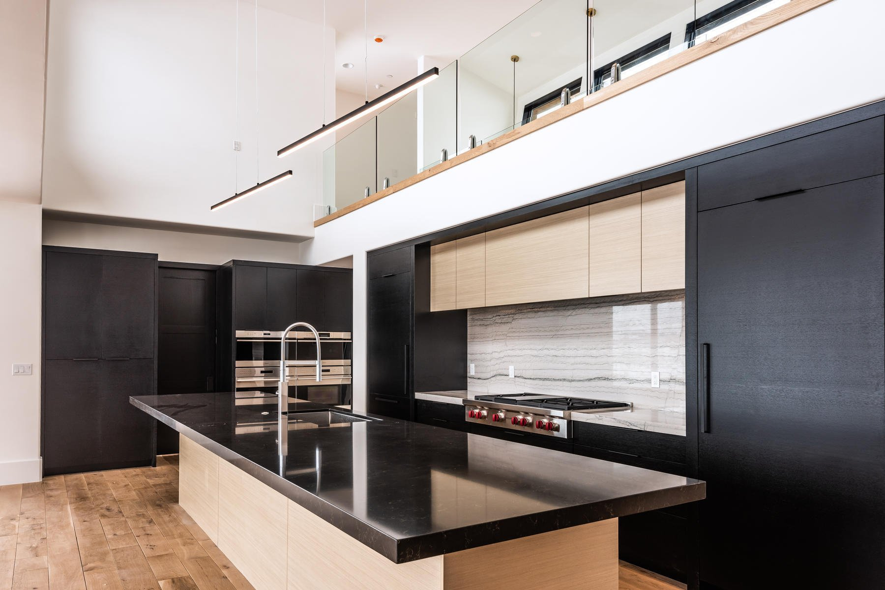 Ultra modern kitchen with a two color cabinet design. Light wood with black.