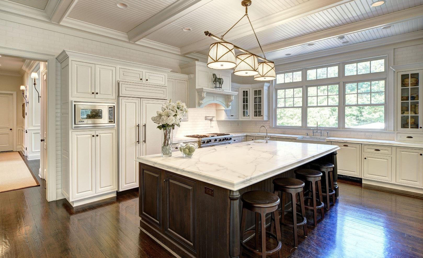Cream colored kitchen cabinets with a rich brown island and matching stools. Marble countertops.