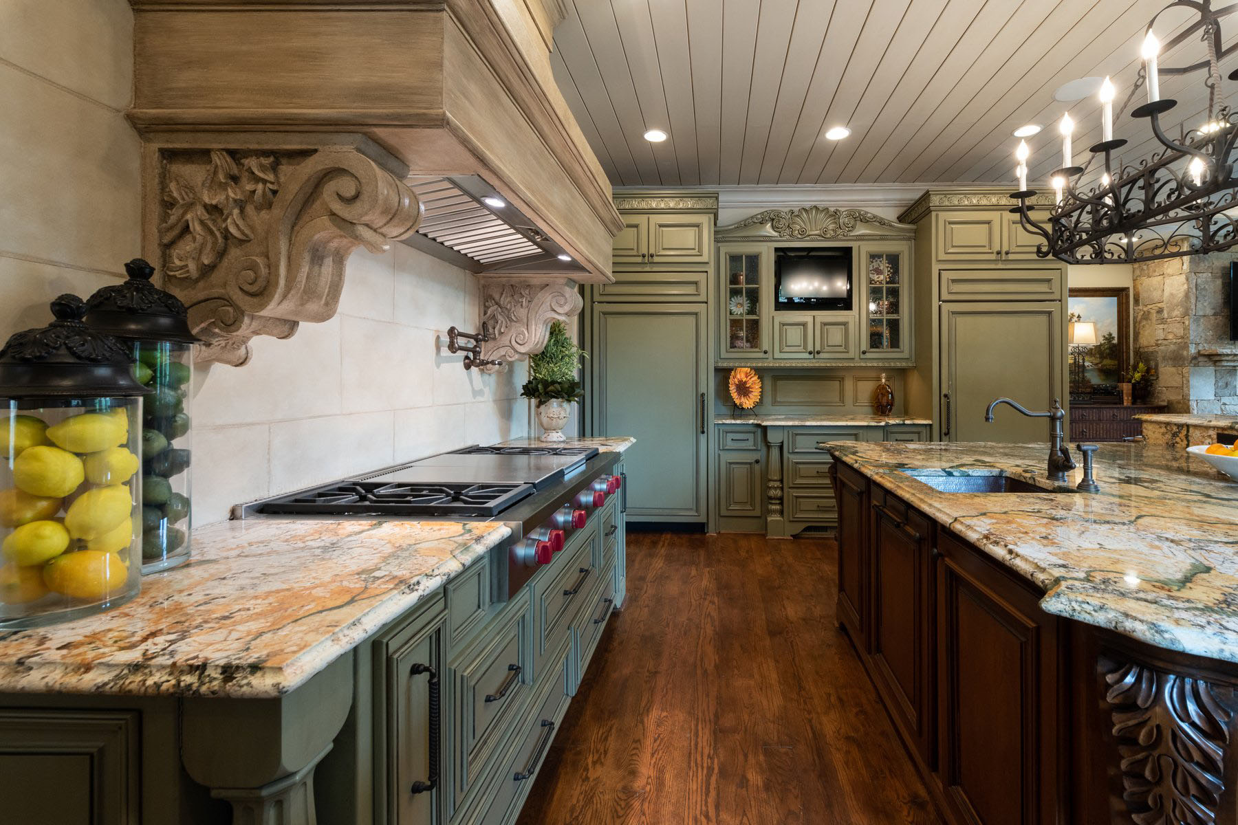 Country style kitchen featuring olive green cabinets paired with a stained dark brown island, warm stone backsplash, medium hardwood floors and granite counters.