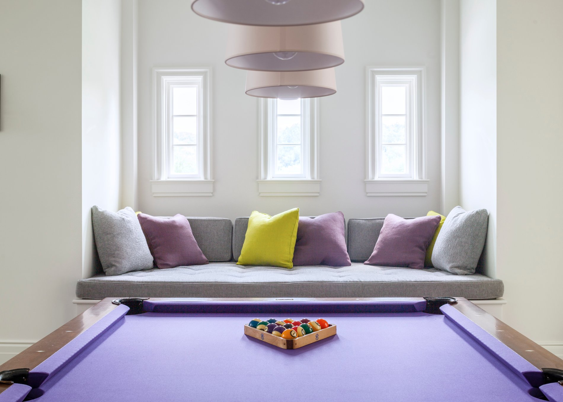 Modern window seat in front of 3 rectangular windows in a game room featuring a purple pool table.