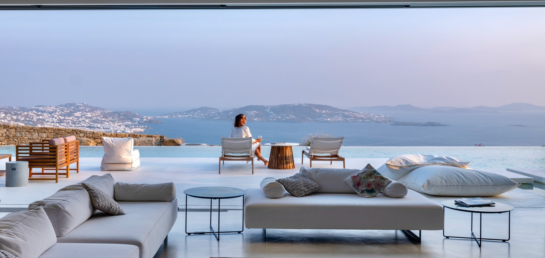Modern Greek Home Mykonos. View from inside the home overlooking the infinity edge pool and Greece.