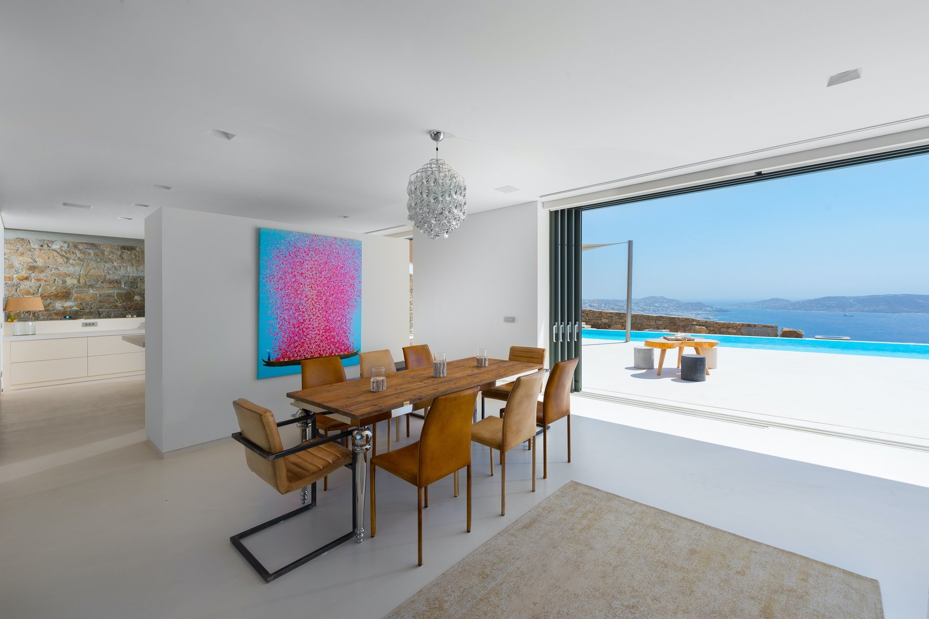 Dining area with a real wood table and chairs for 8 and a stunning view of the Mediterranean.