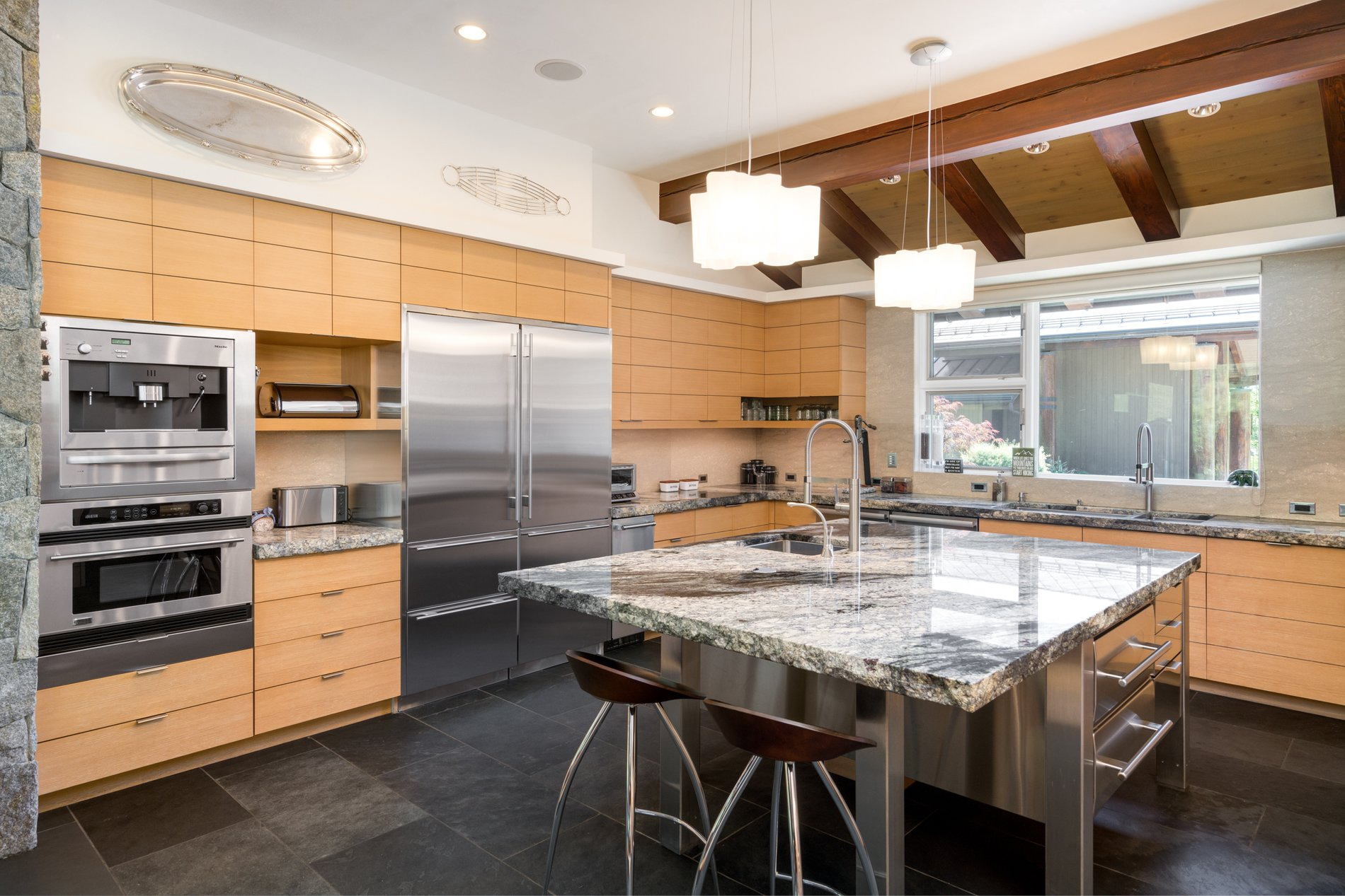Stainless steel appliances with built in ovens. modern rustic home.