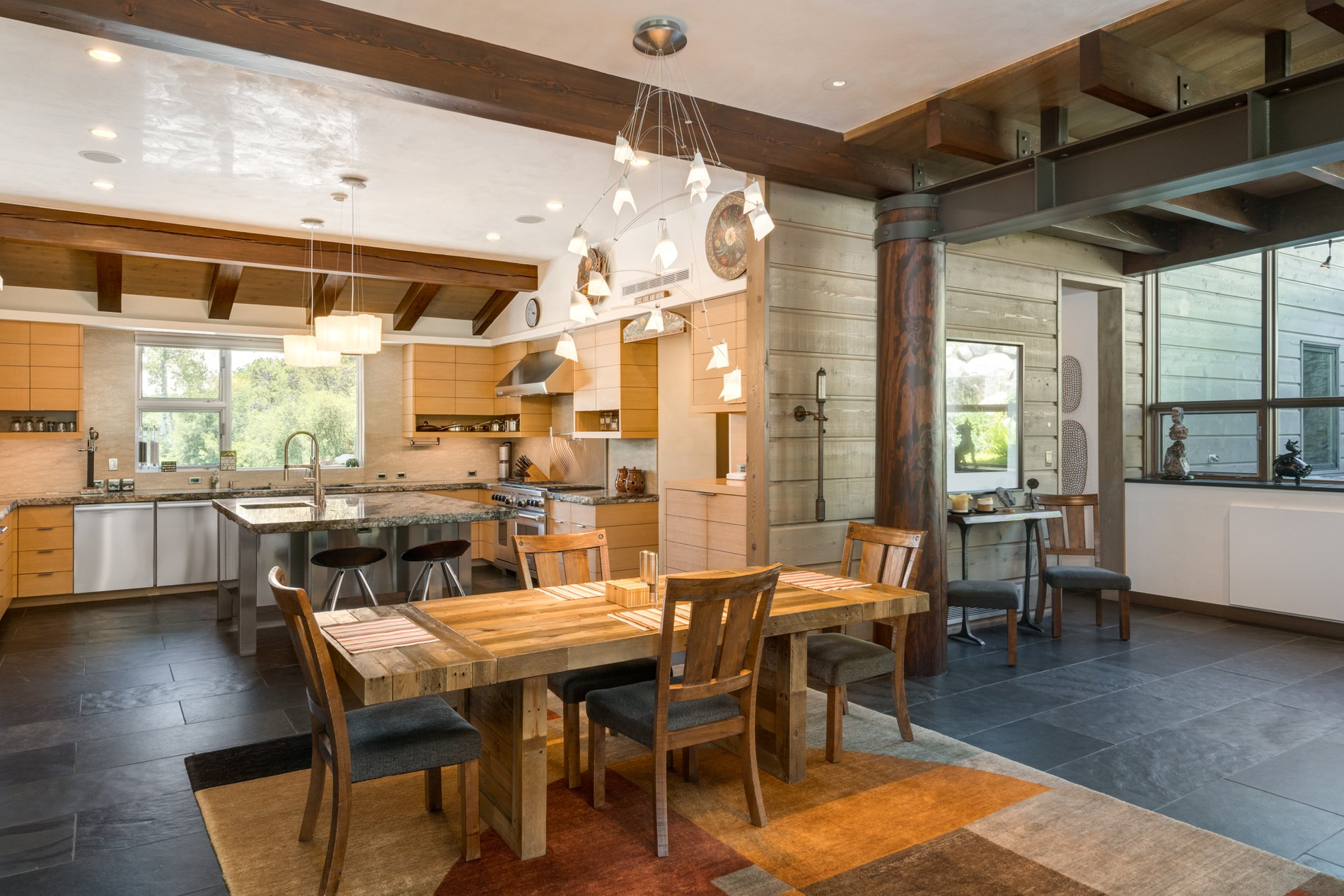 Open floor plan kitchen and eating area with lots of real wood using all sorts of finishes and stains. modern rustic home.