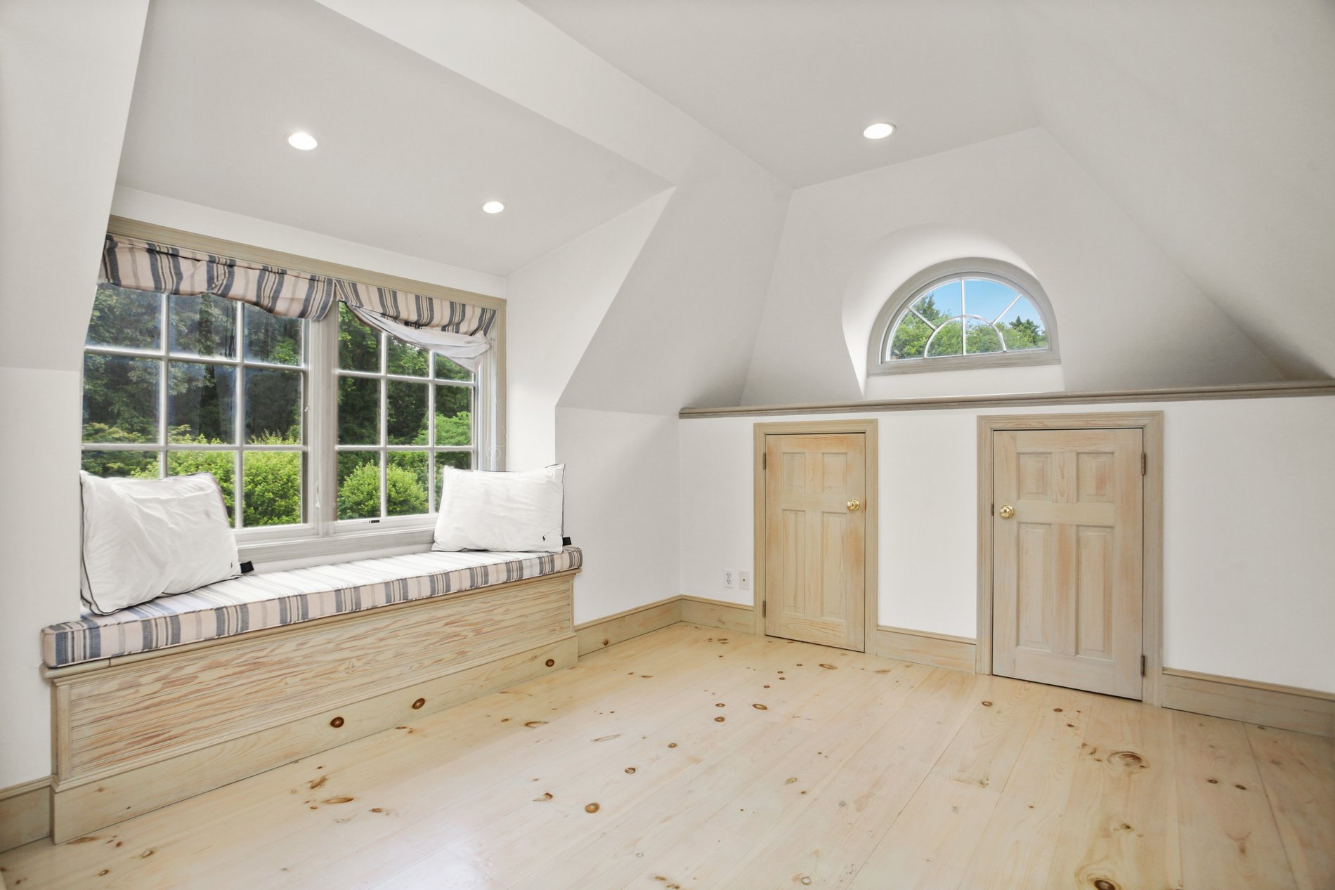 Rustic country style finished attic with wide plank knotty pine floors and a high window seat.