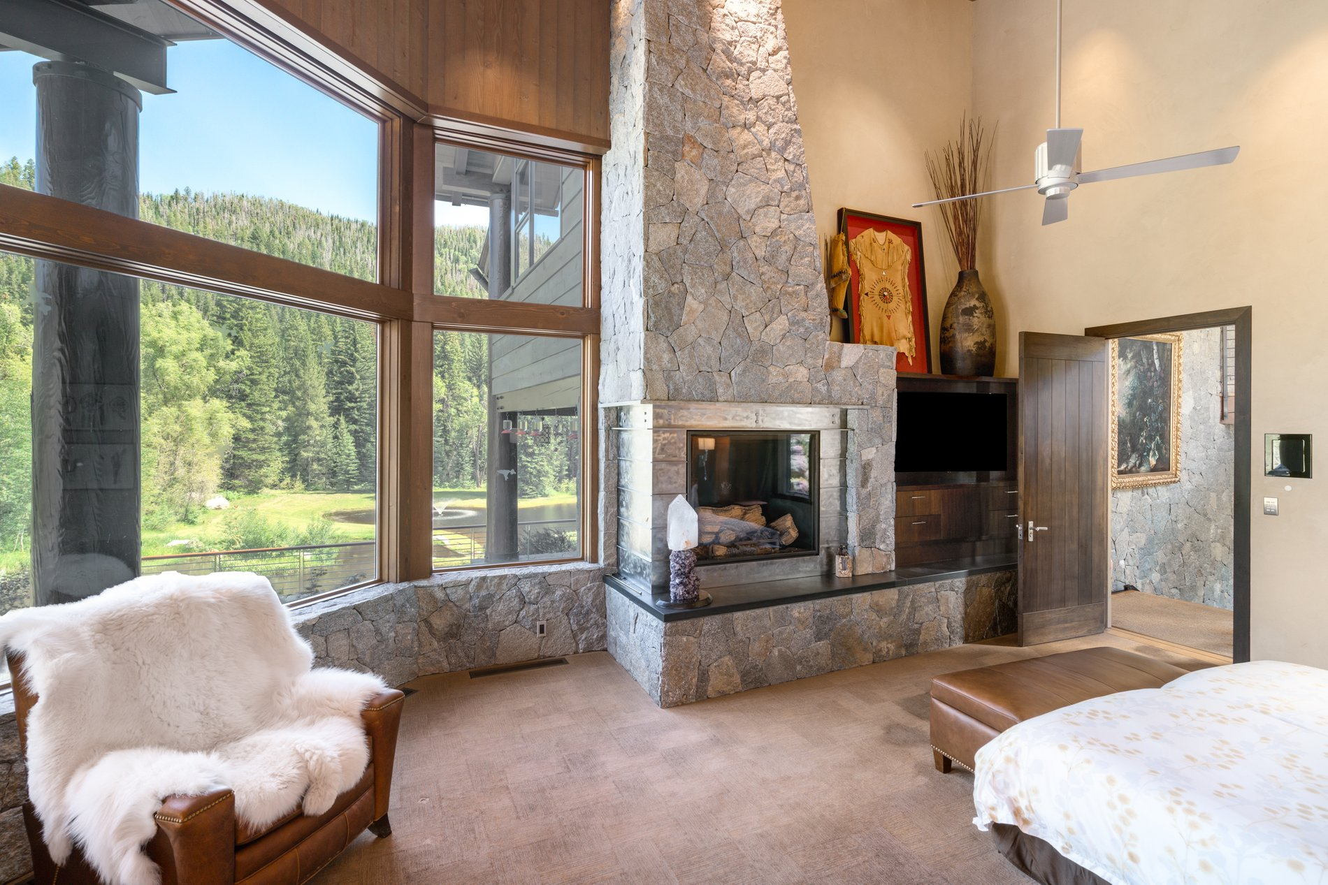 Real stone master bedroom fireplace with wood burning firebox.