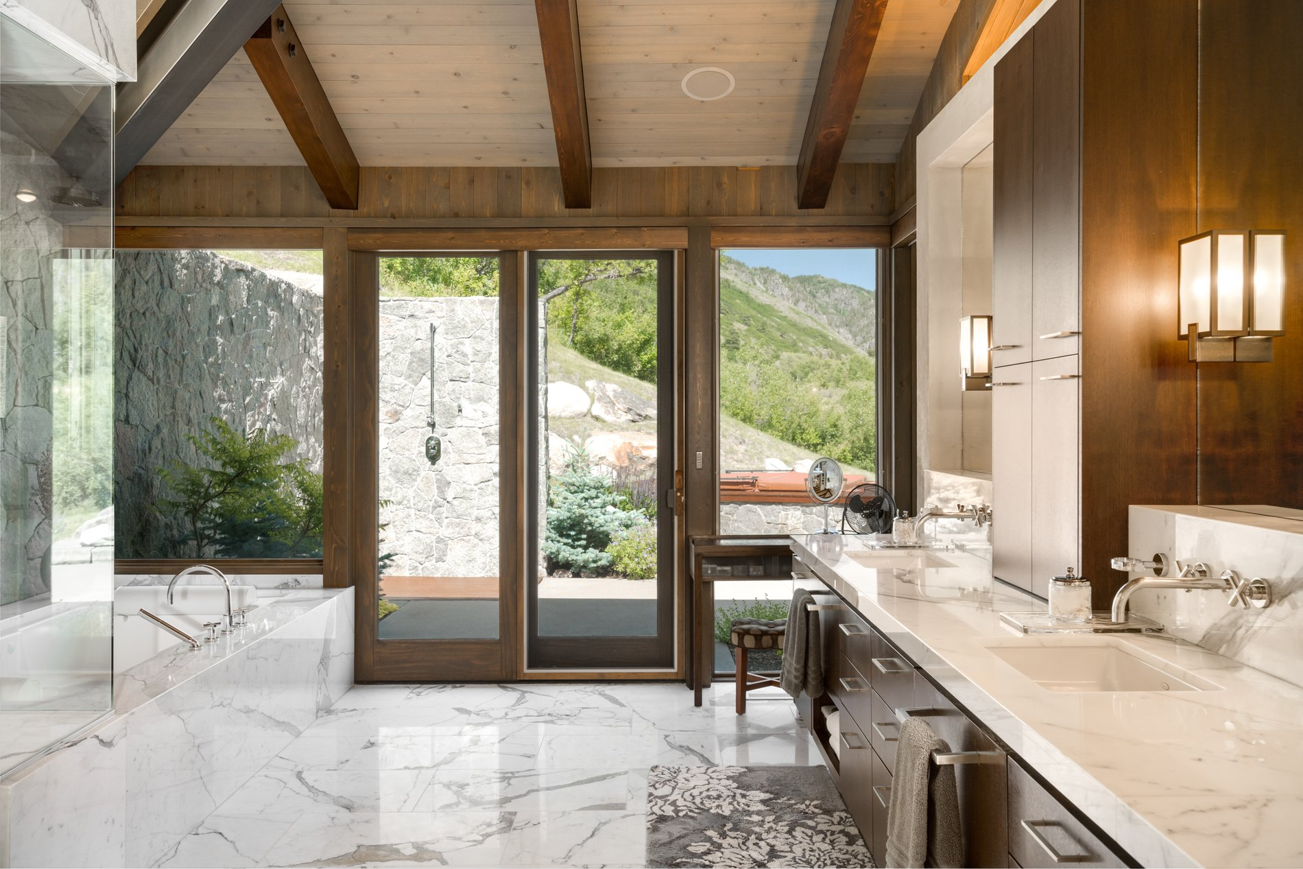 Beautiful luxury master bathroom with a private balcony, lots of marble and double sinks. modern rustic home.