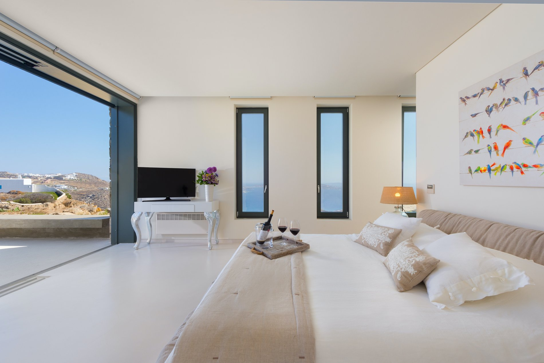 Masted bedroom with a gliding recessed glass door and view of the Mediterranean.