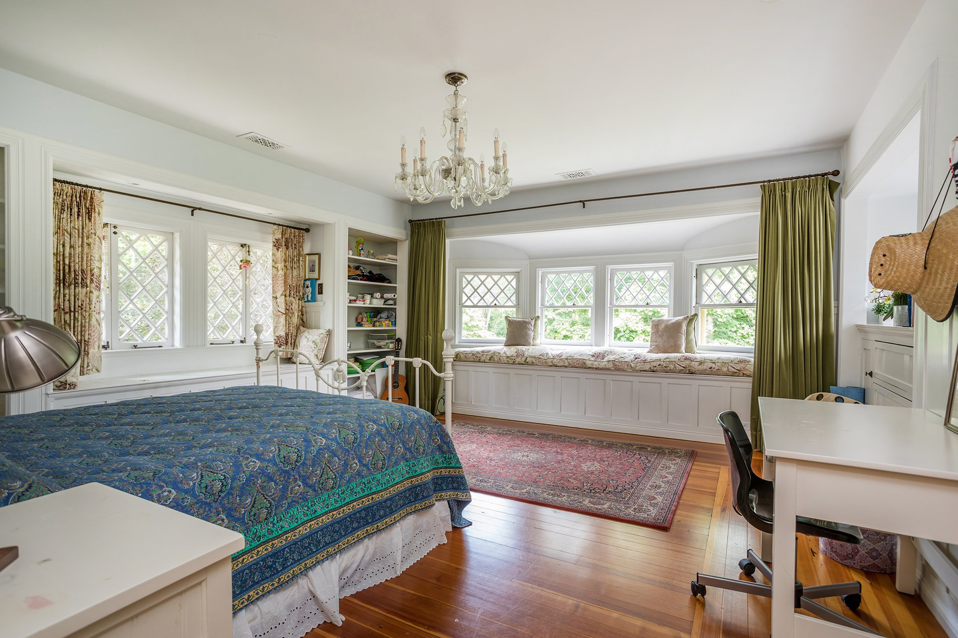 Traditional style master bedroom with a beautiful window seat featuring a single plush patterned cushion.