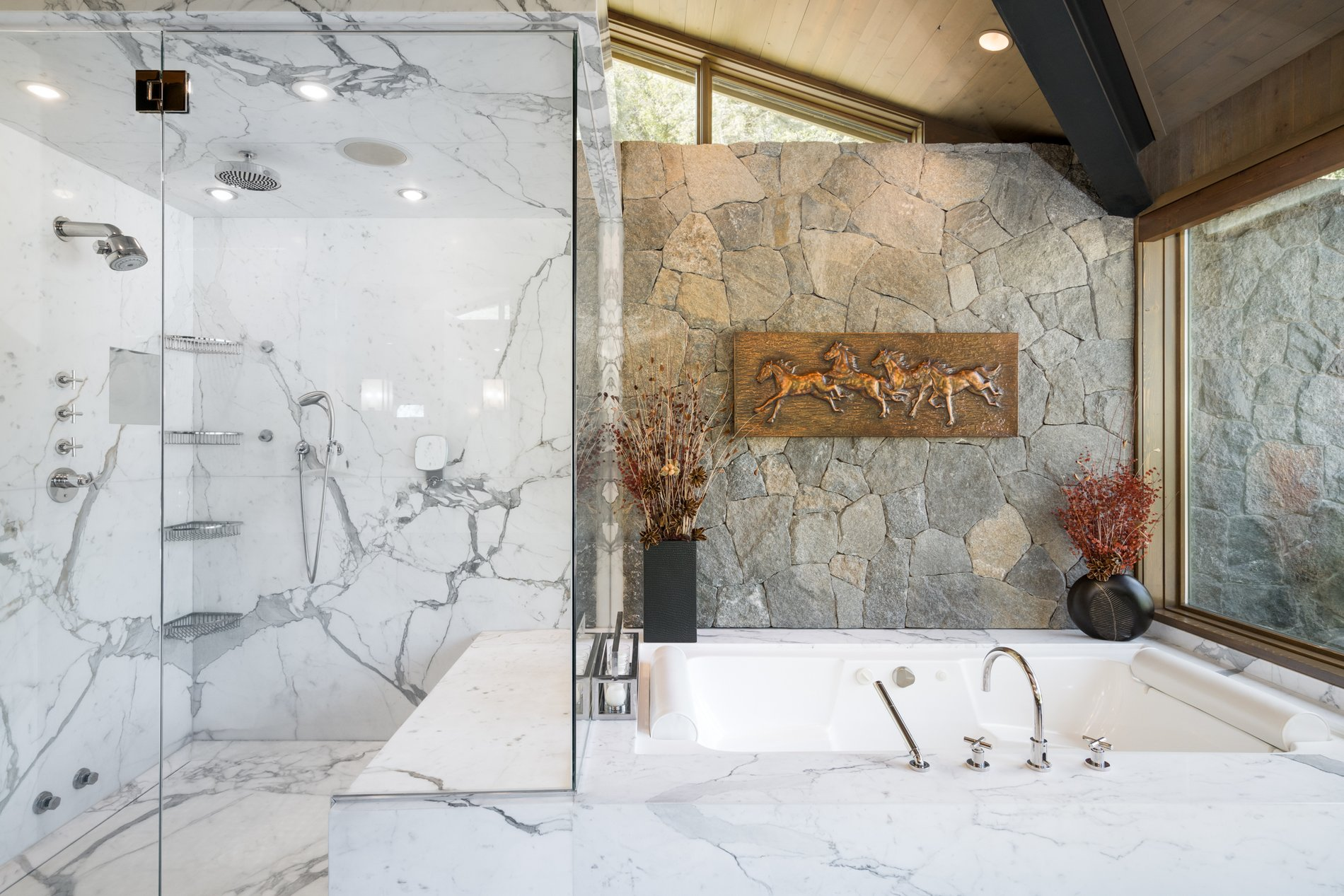 Soaking tub surrounded by marble slabs with a walk in glass enclosed shower and stone wall.
