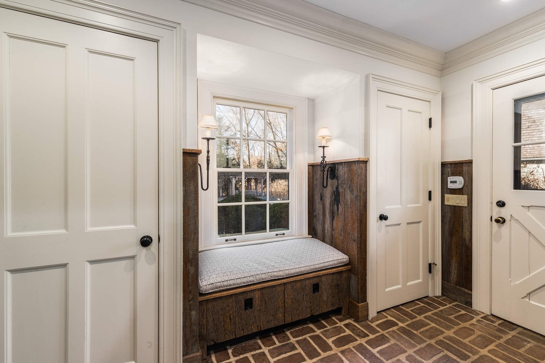 Rustic country style window seat in a mudroom featuring a bench seat with cushion, storage and real wood.