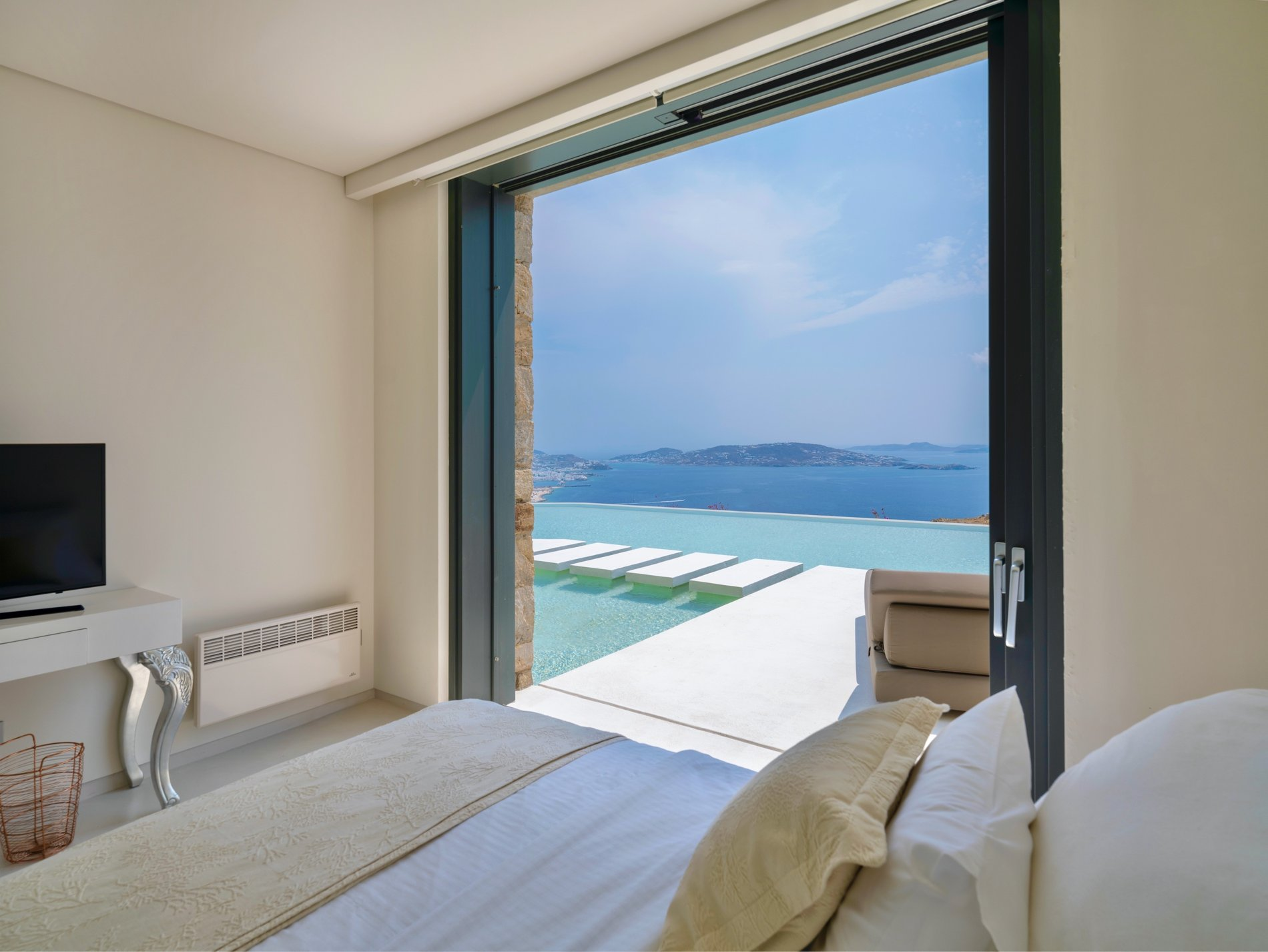 Bedroom with gliding patio door, access to the infinity pool and Mediterranean views.