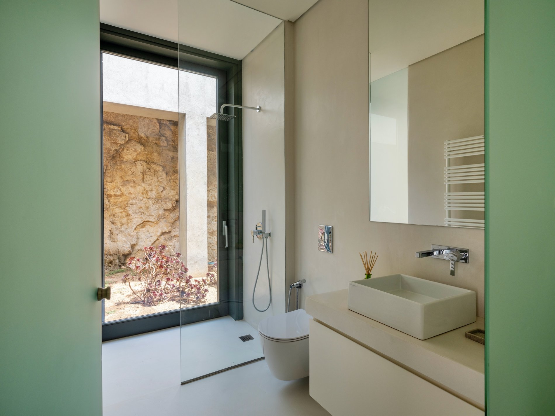Bathroom finished with cement floors and walls. Modern design with a glass wall.