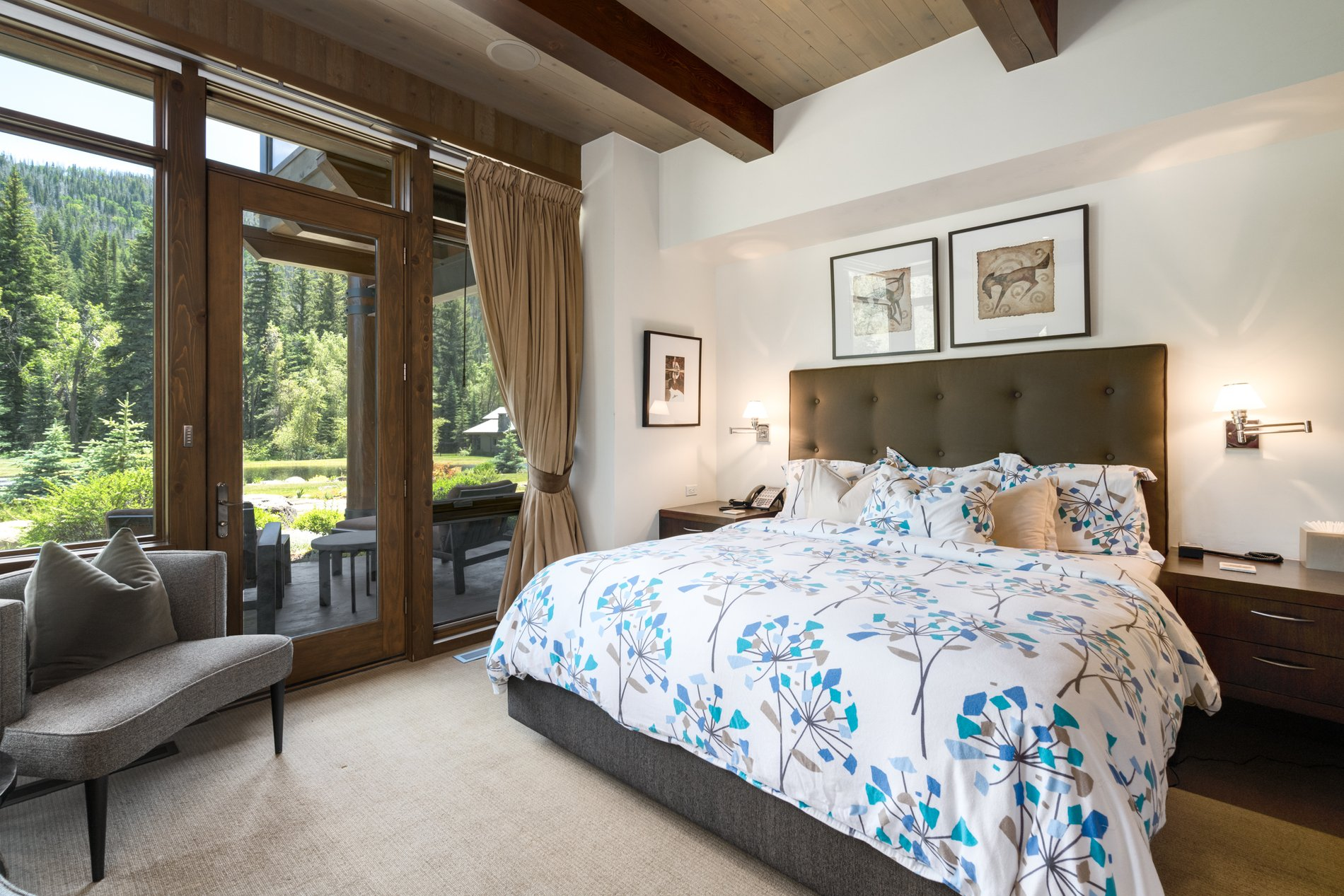 Beautiful guest bedroom with walkout patio area, raised ceilings, exposed timber beams and a wood ceiling.