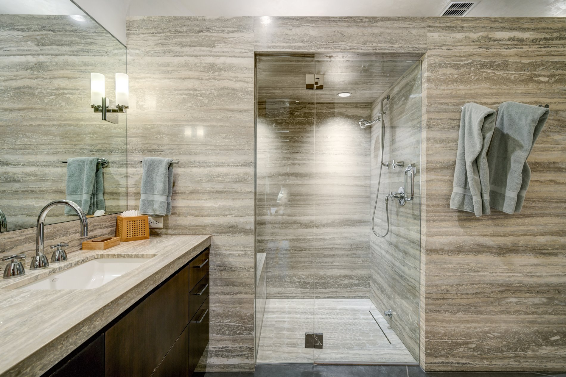 Another fantastic bathroom finished with stone slabs, real wood, tile and glass.