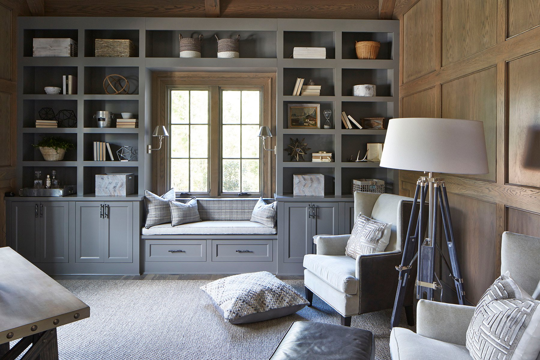 Window seat in a home office built between two built in shelves and cabinetry.
