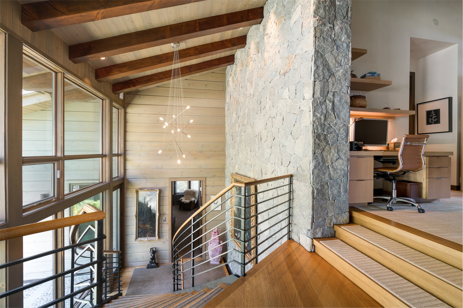 Modern winding staircase in front of the two story wall of glass. Metal railings with a wood hand rail. modern rustic home.