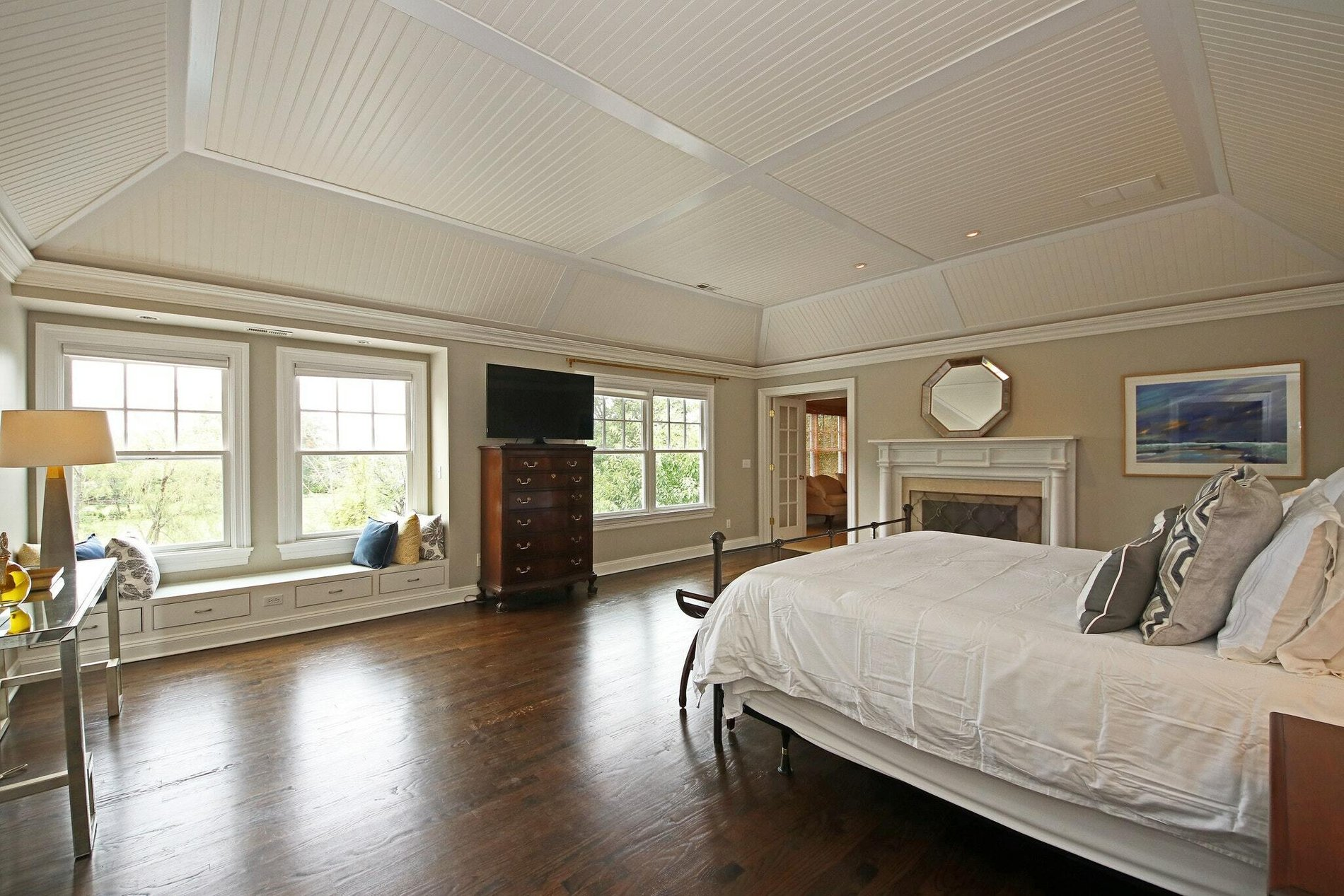 Large master bedroom with a cream colored window seat above built in drawers.