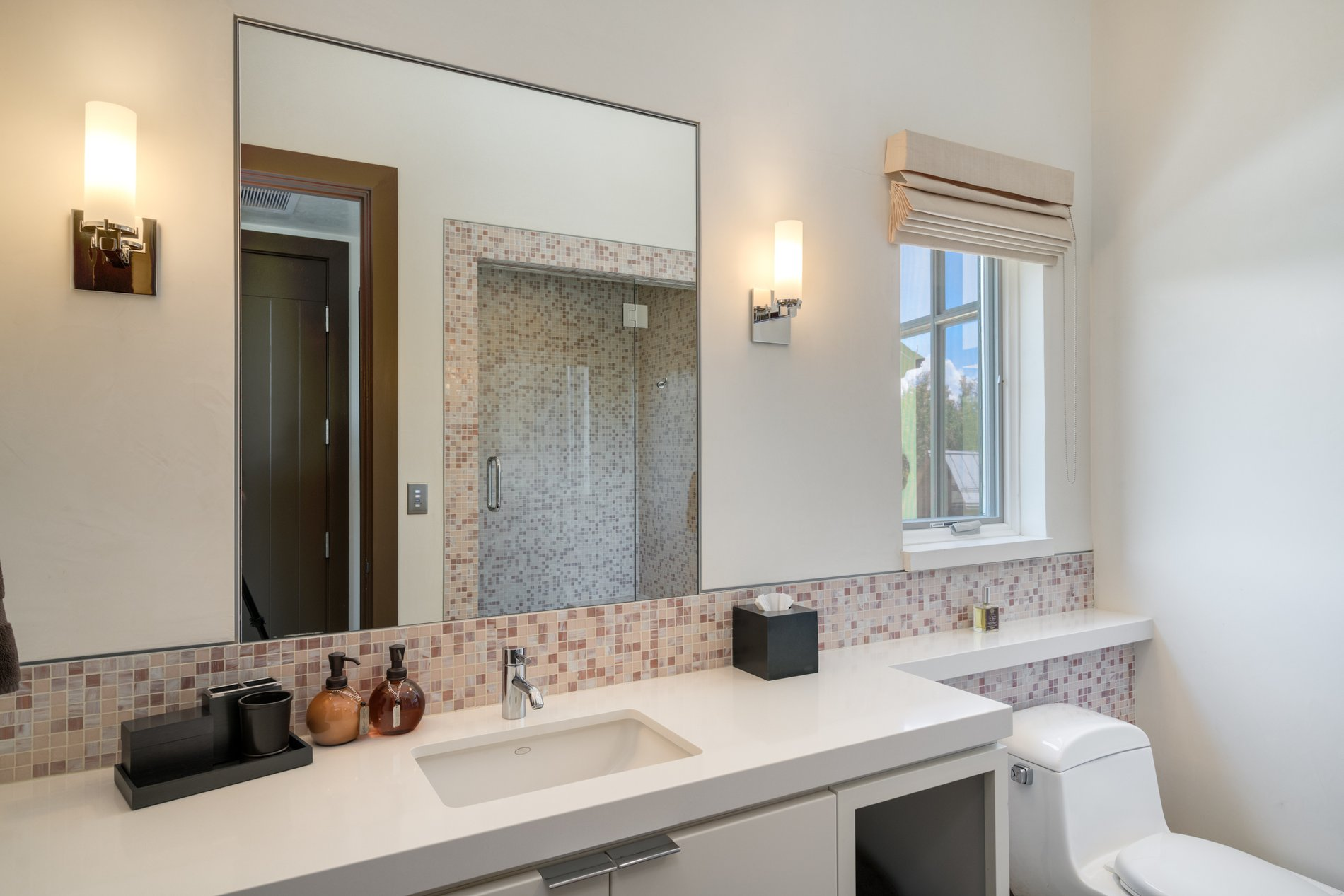 Half bath with a single sink, stone counter, flat faced cabinetry and tile backsplash. It's a cute bathroom that's just the right size for guests.