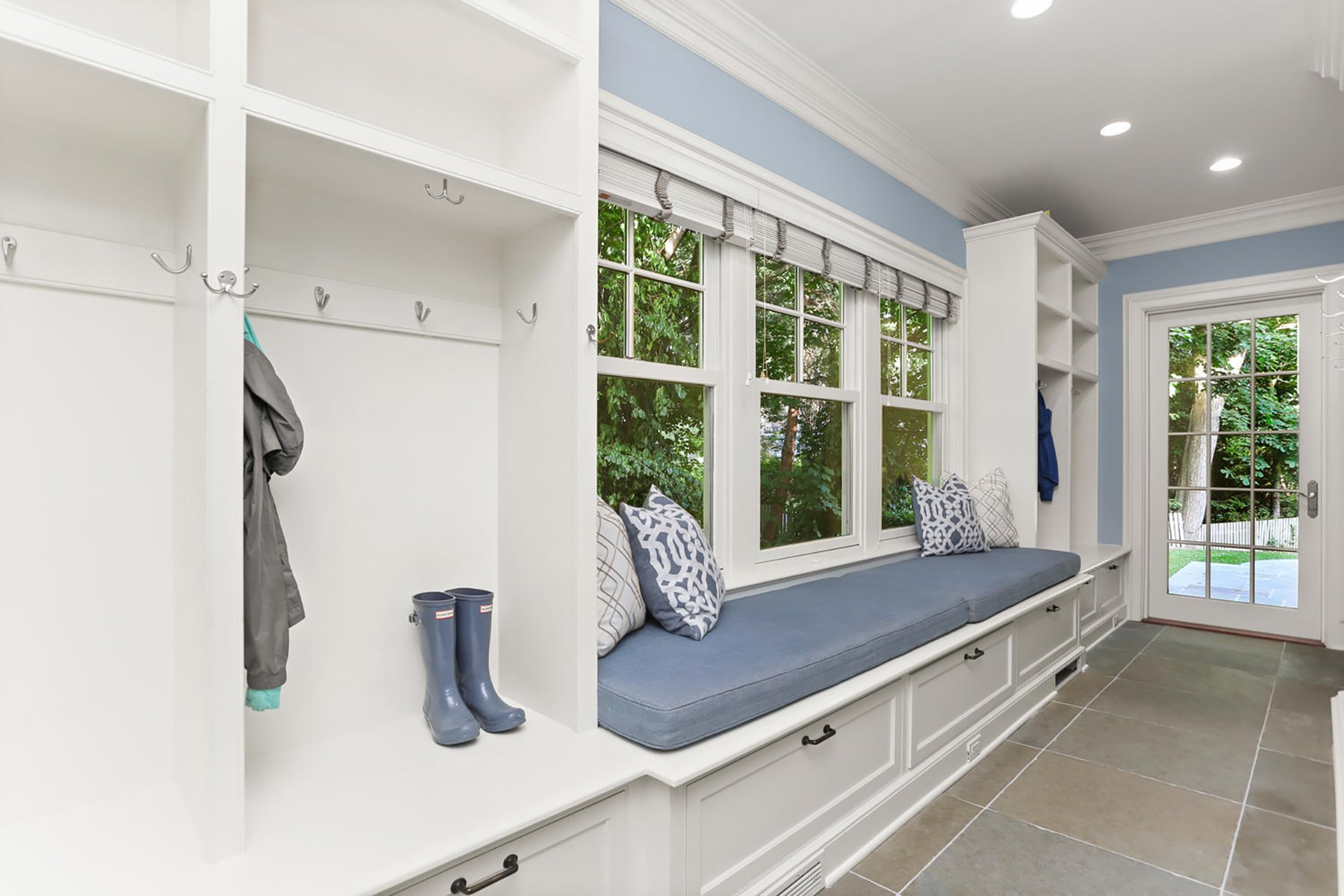 Mudroom window seat with storage bin base. Blue cushion with throw pillows.