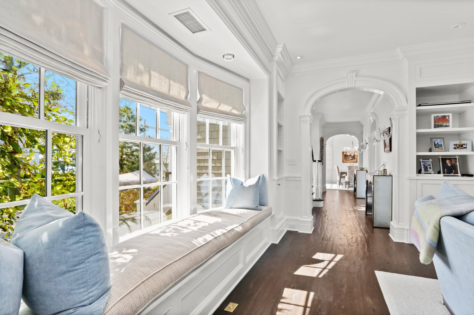 Beautiful white living room with a bay window featuring a plush cushion seat and pale blue throw pillows.