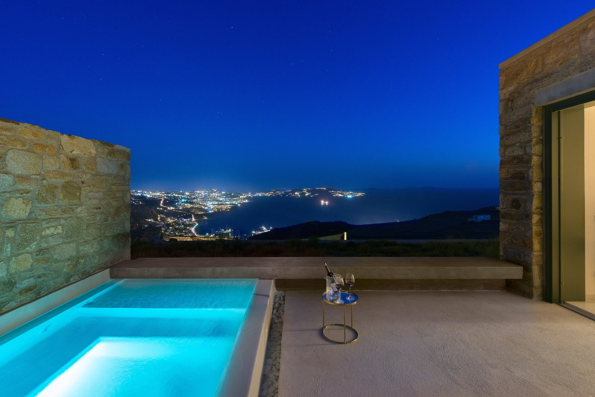 Private hot tub surrounded by real stone walls and concrete with views of Mykonos and the Mediterranean.