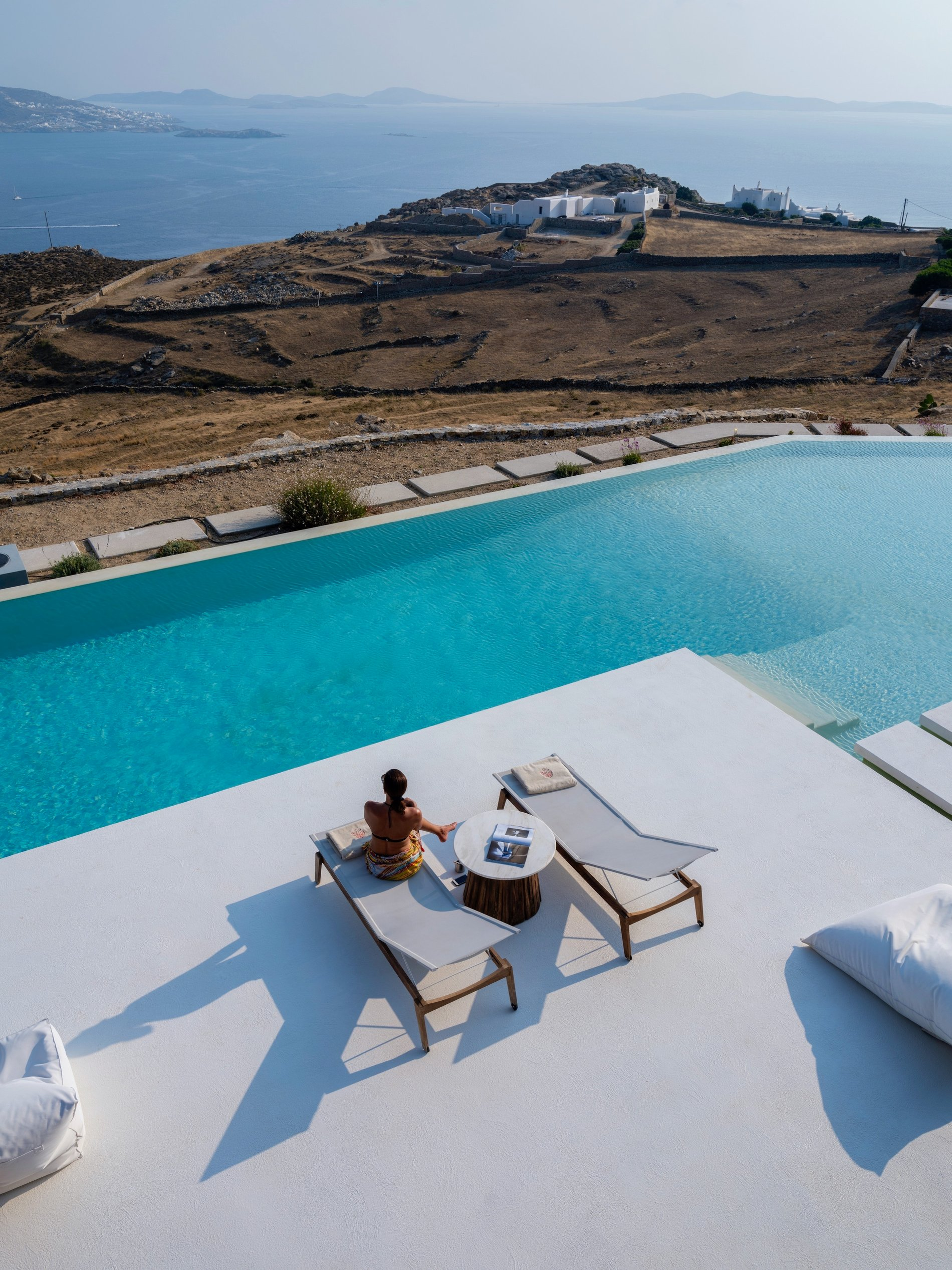 Ariel view of the patio, pool and land separating this stunning Modern home from the Mykonos shoreline.