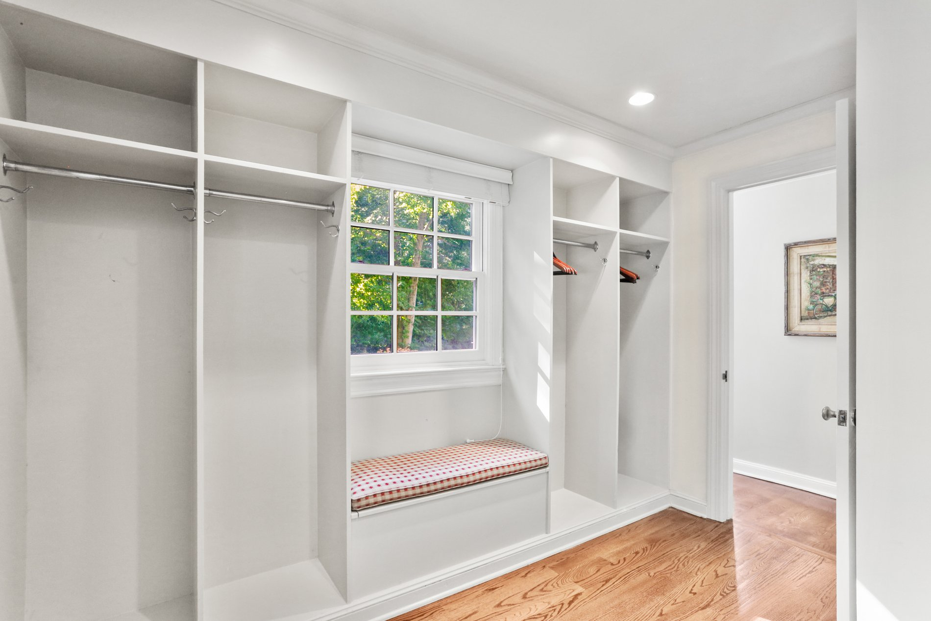 Simple window seat in a mudroom with red and white spotted cushion.
