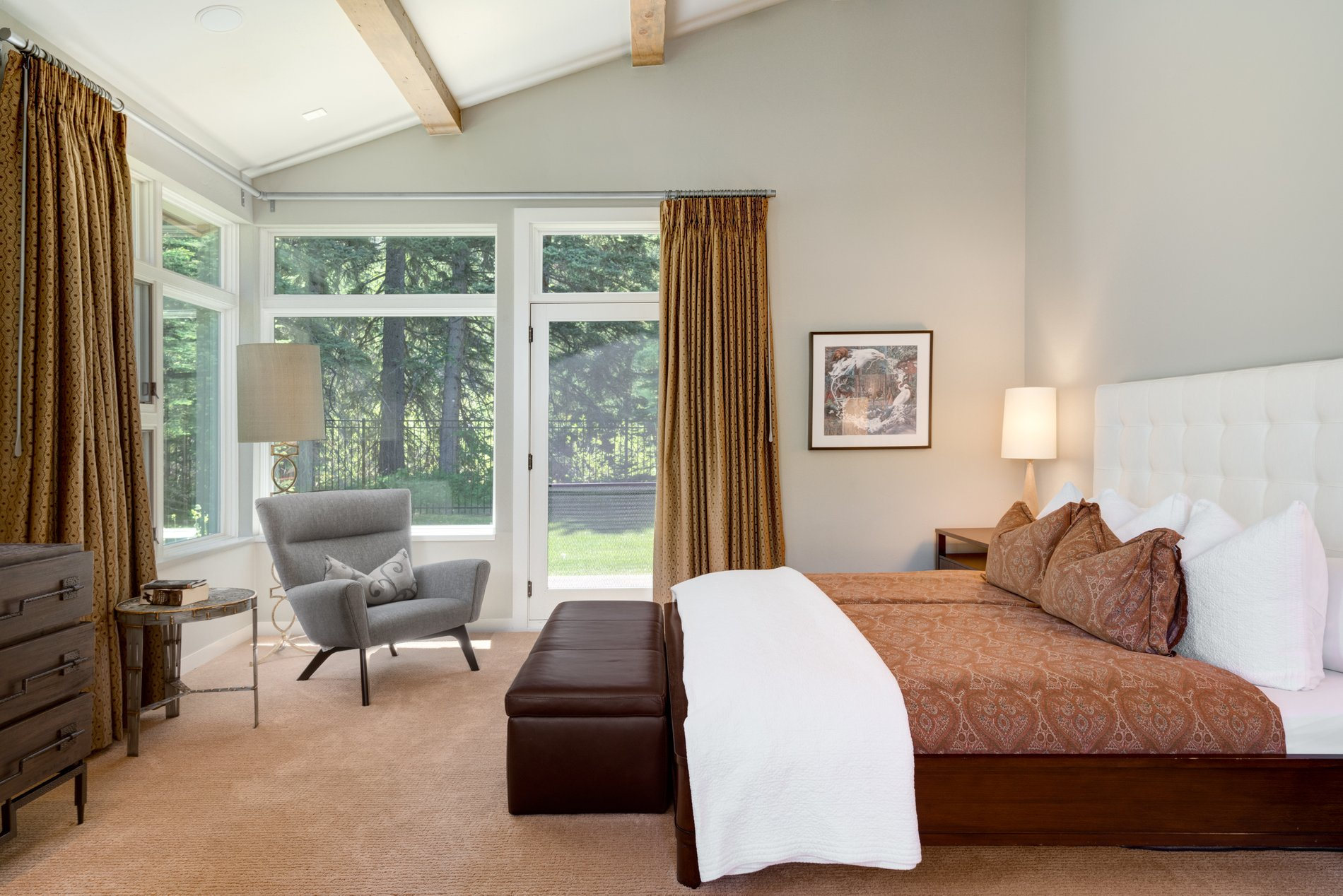 Guest bedroom featuring a vaulted ceiling with exposed timber beams. Walk out to the patio area.