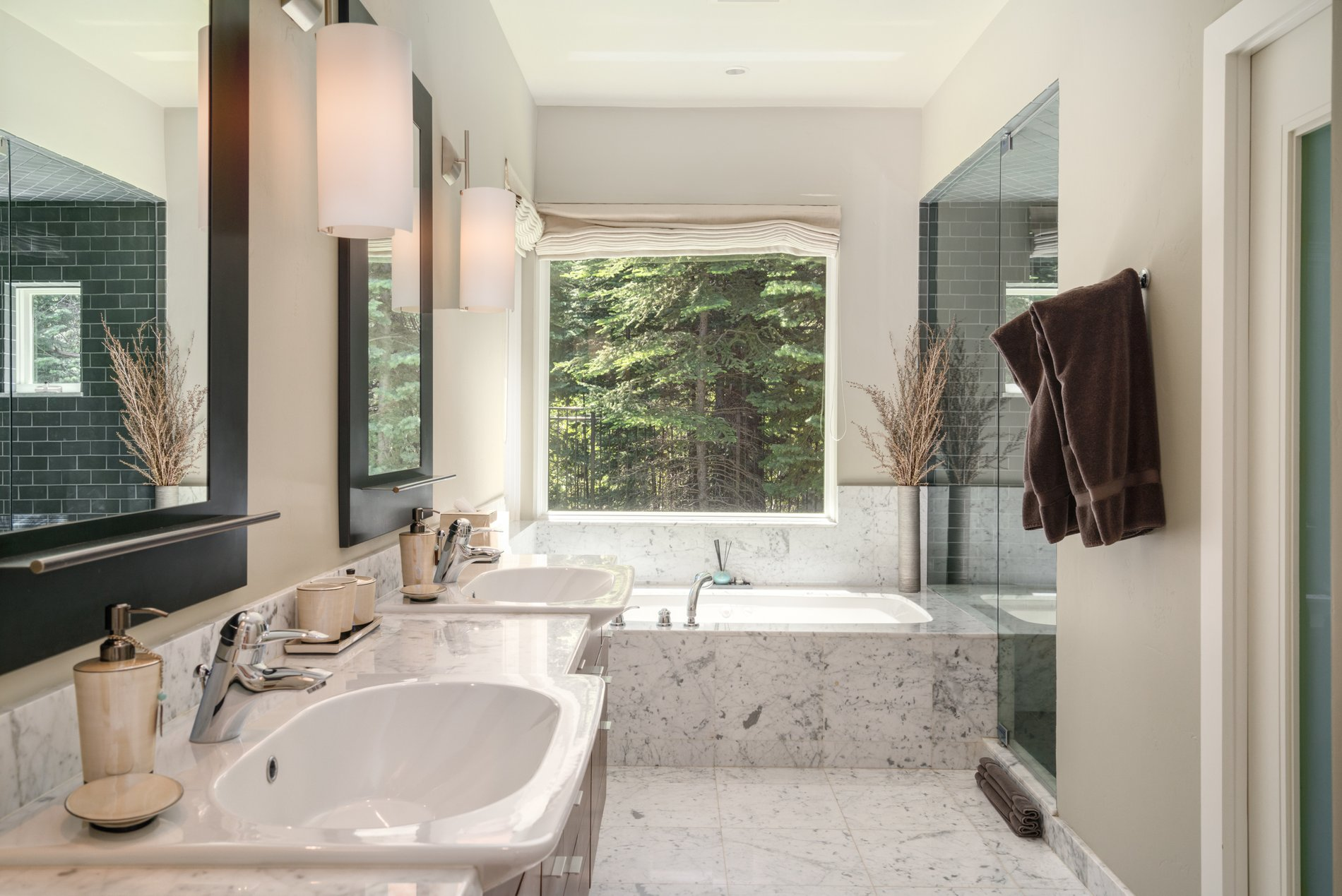 A more traditionally styled bathroom with marble, tile, double sinks, wood cabinetry and a walk in shower.
