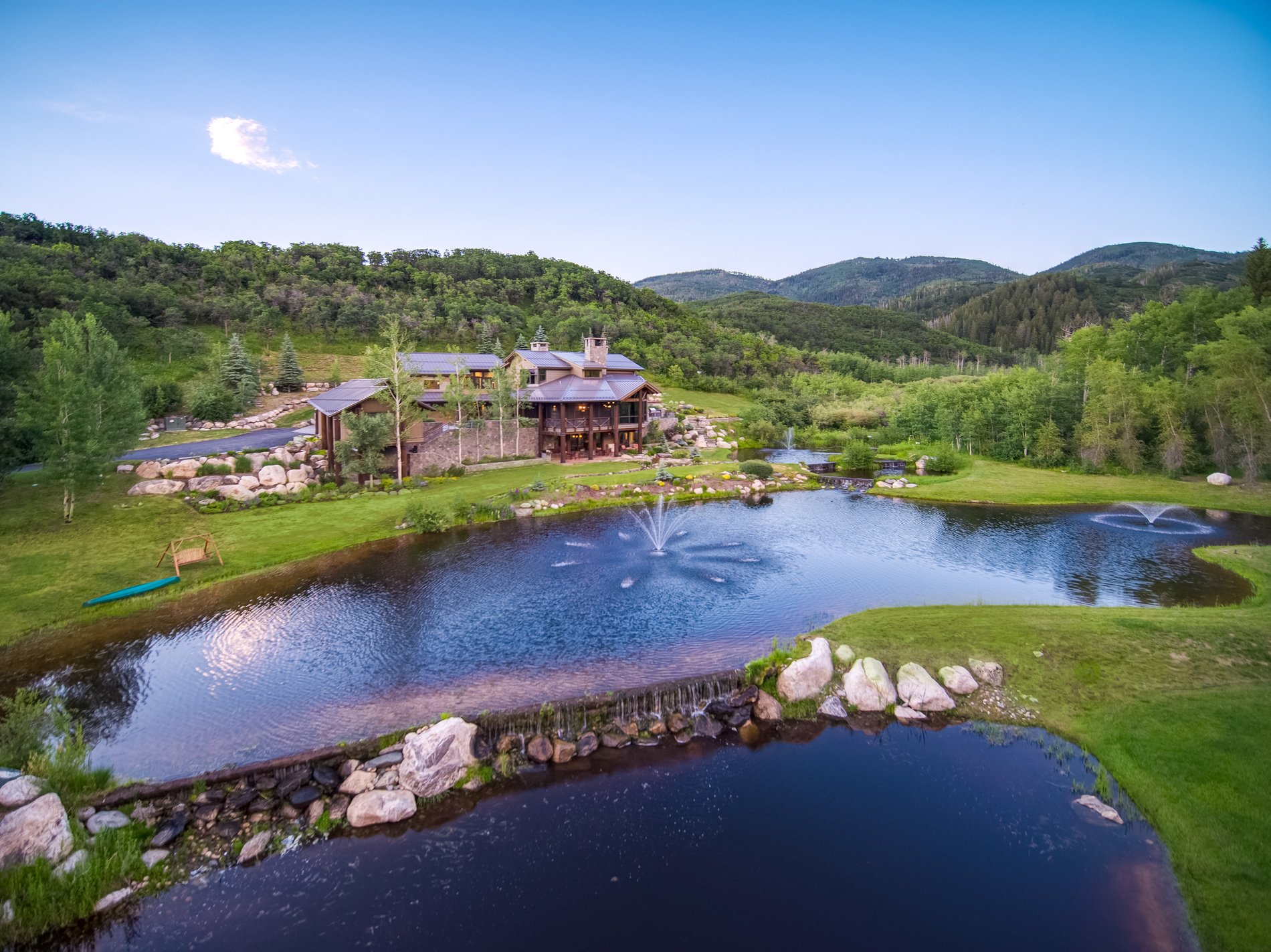 Lake and waterfalls with fountain. Custom modern rustic home in Colorado.
