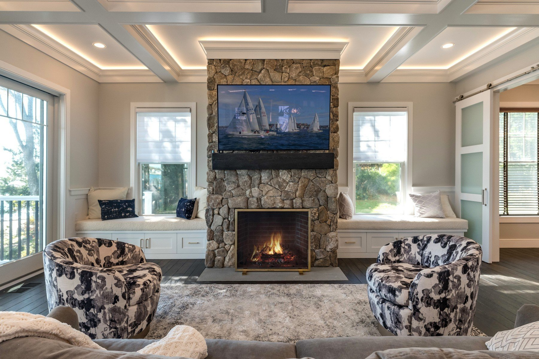 Living room with a wood burning fireplace surrounded by window seating.