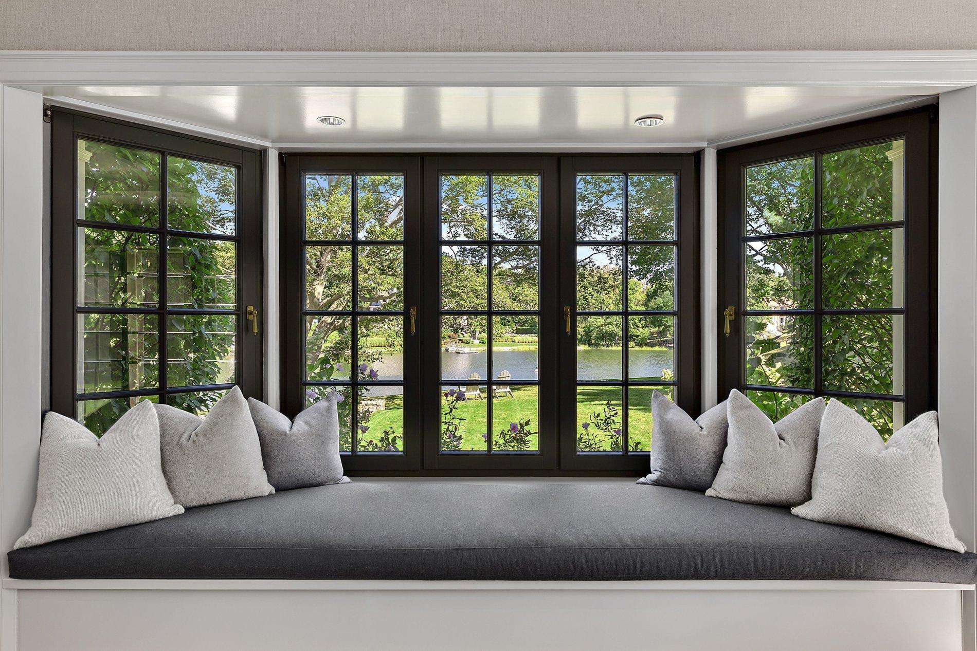 Modern bay window seat featuring a dark grey cushion, light grey pillows and black frame windows.