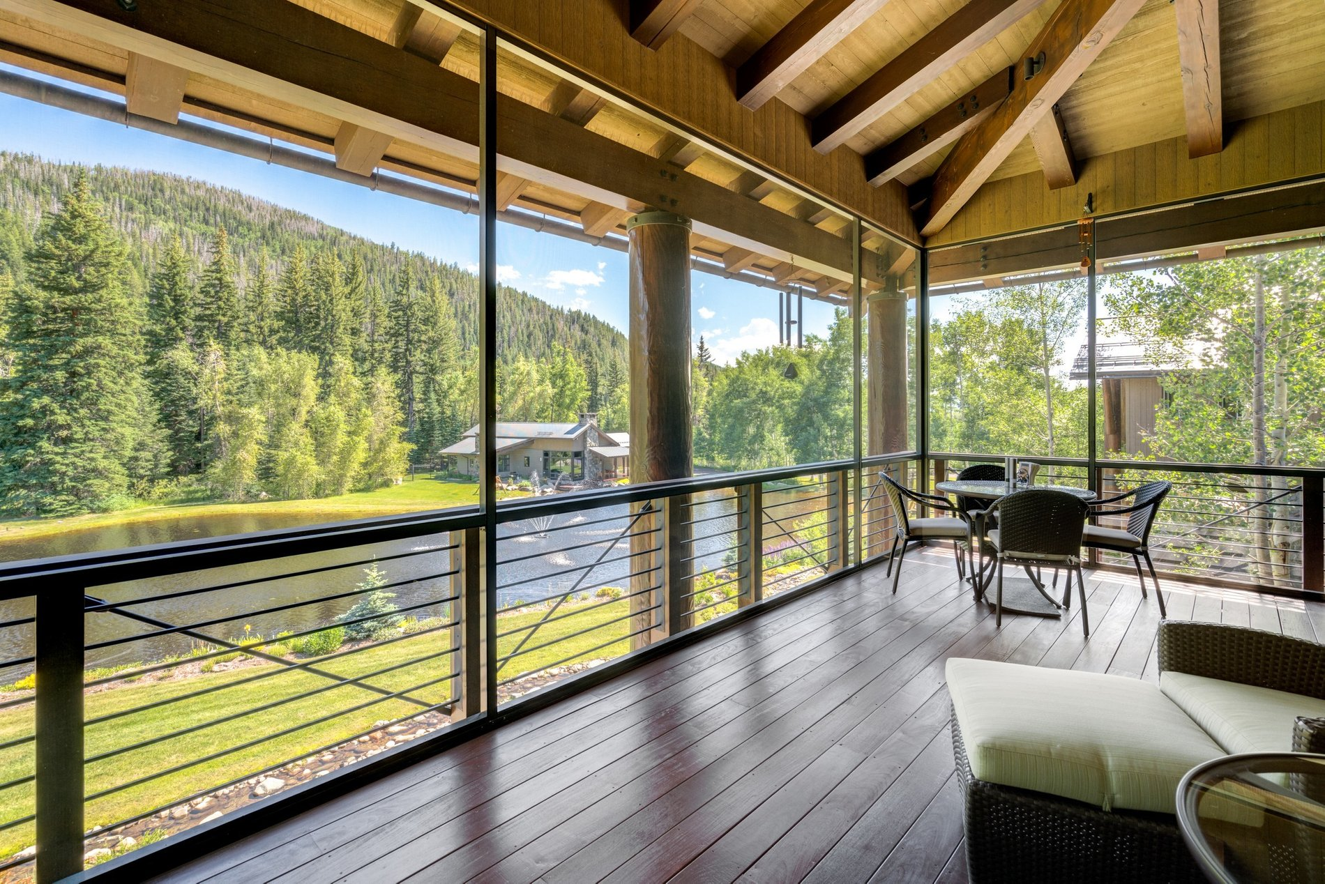 A covered deck overlooking the lake and countryside with real wood decking and ceiling beams. modern rustic home.