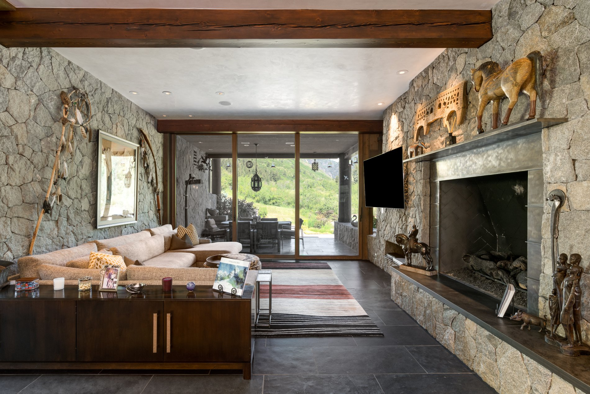 Huge wood burning fireplace with a real stone wall and raised hearth stone.
