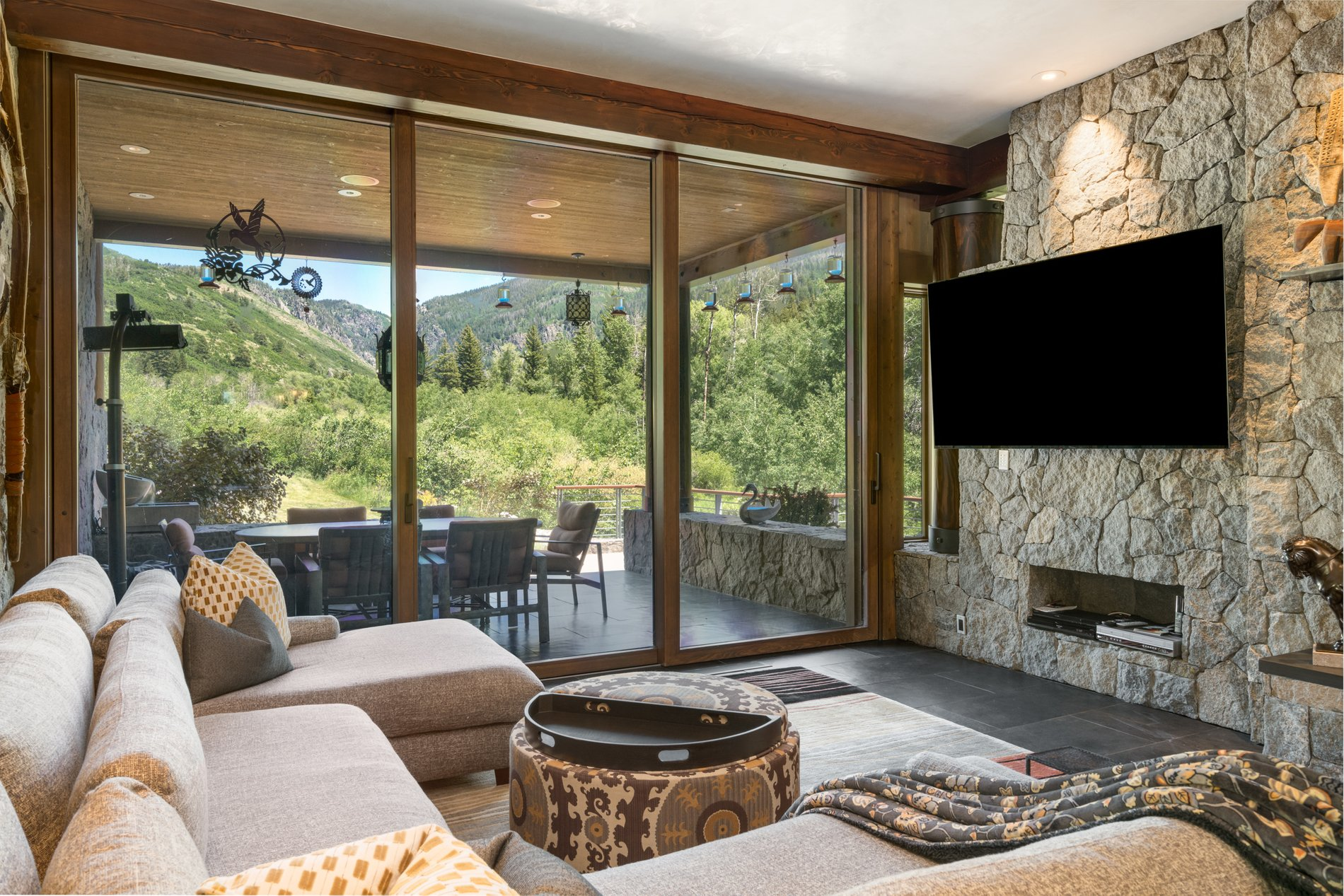 Indoor/outdoor living room leading to a covered patio area. Gliding wood patio doors from floor to ceiling. modern rustic home.