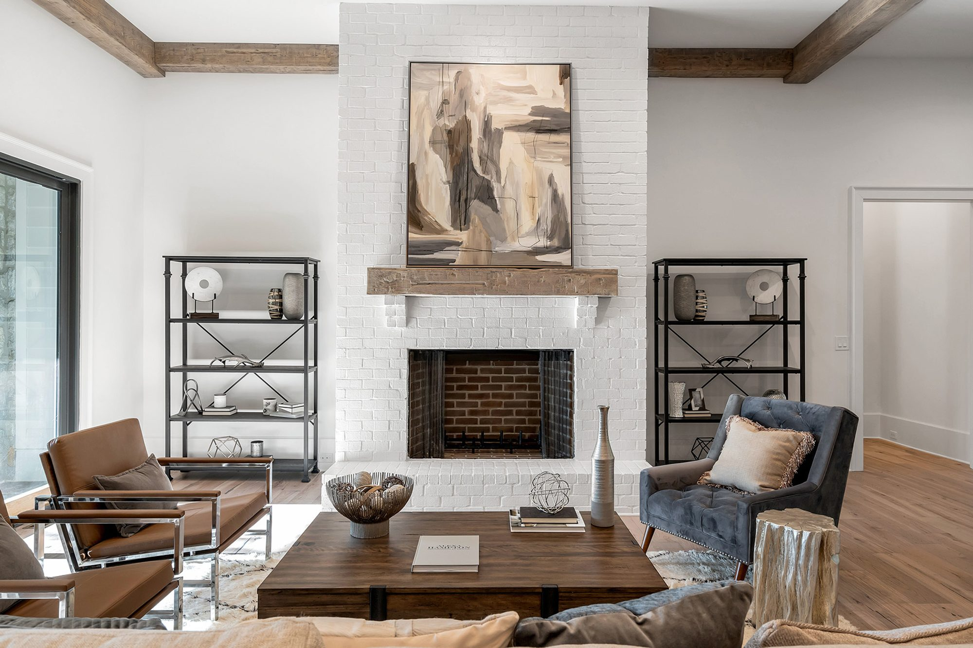 Living room with muted neutral hardwood floors and a white brick wood burning fireplace.