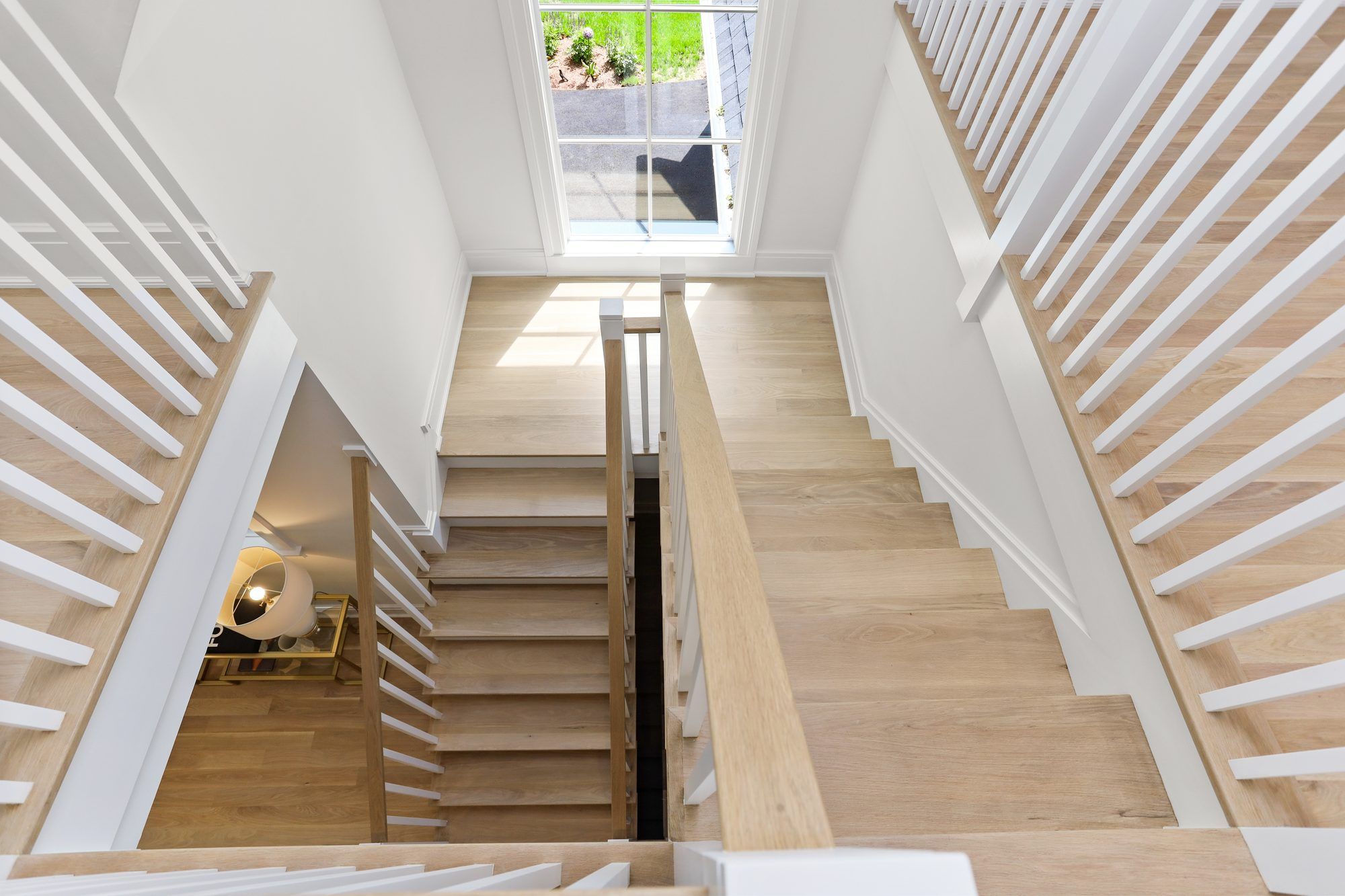 Lightly stained pale hardwood floors with matching stairs.