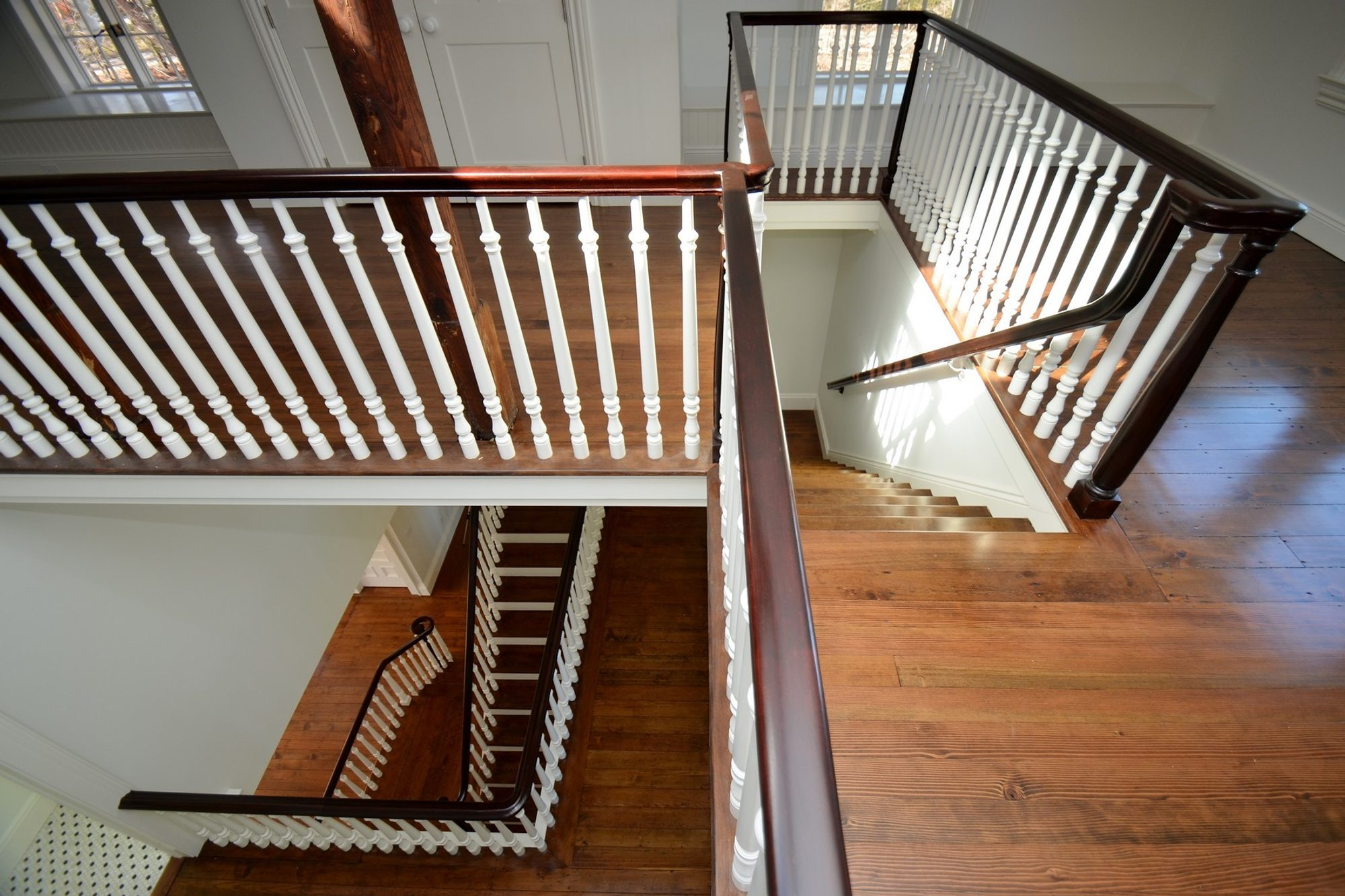 Natural wide plank hardwood floors stained a medium dark brown. Matching wood stairs.