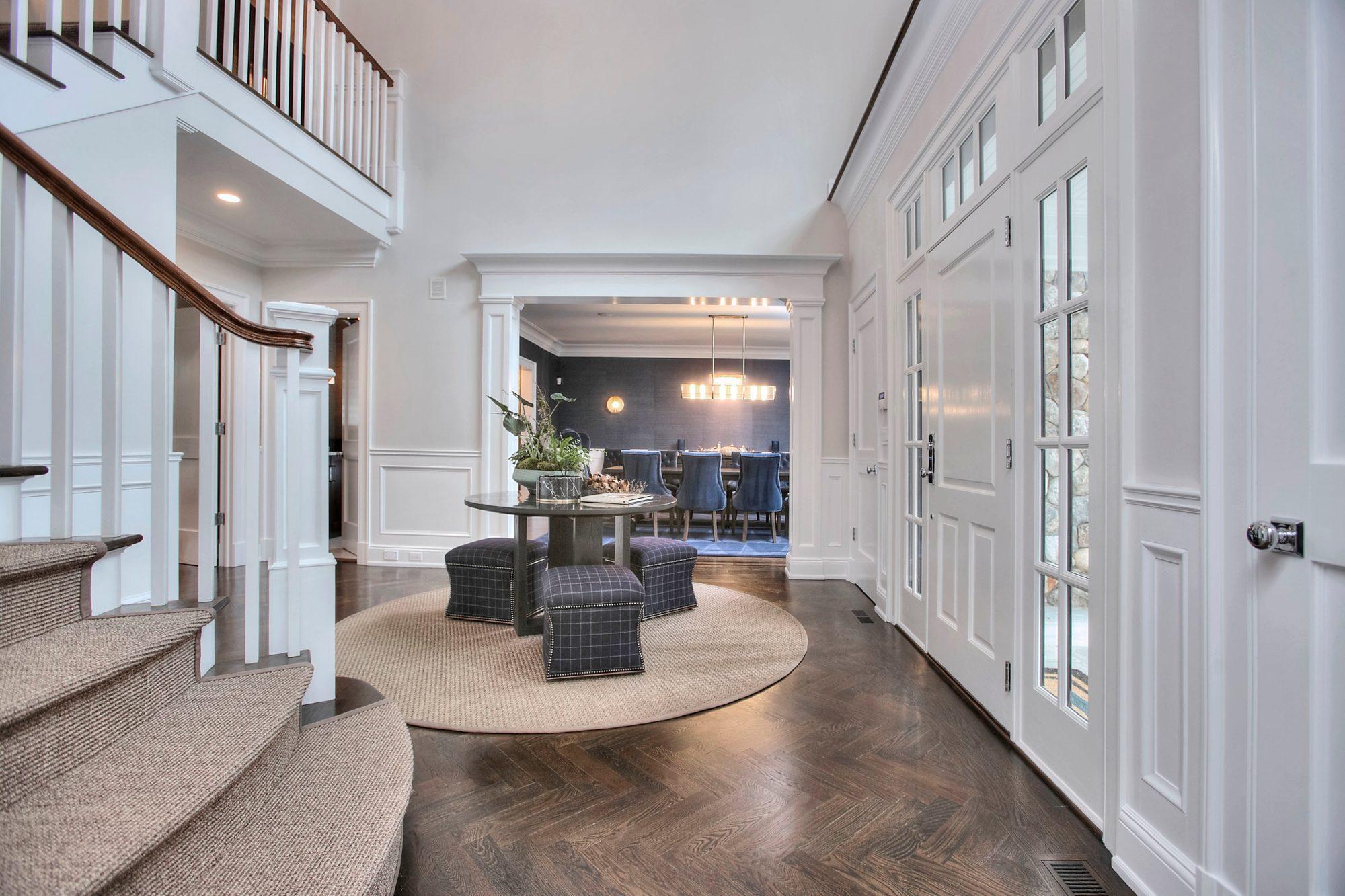 beautiful custom home with dark brown hardwood floors installed with a herringbone pattern.