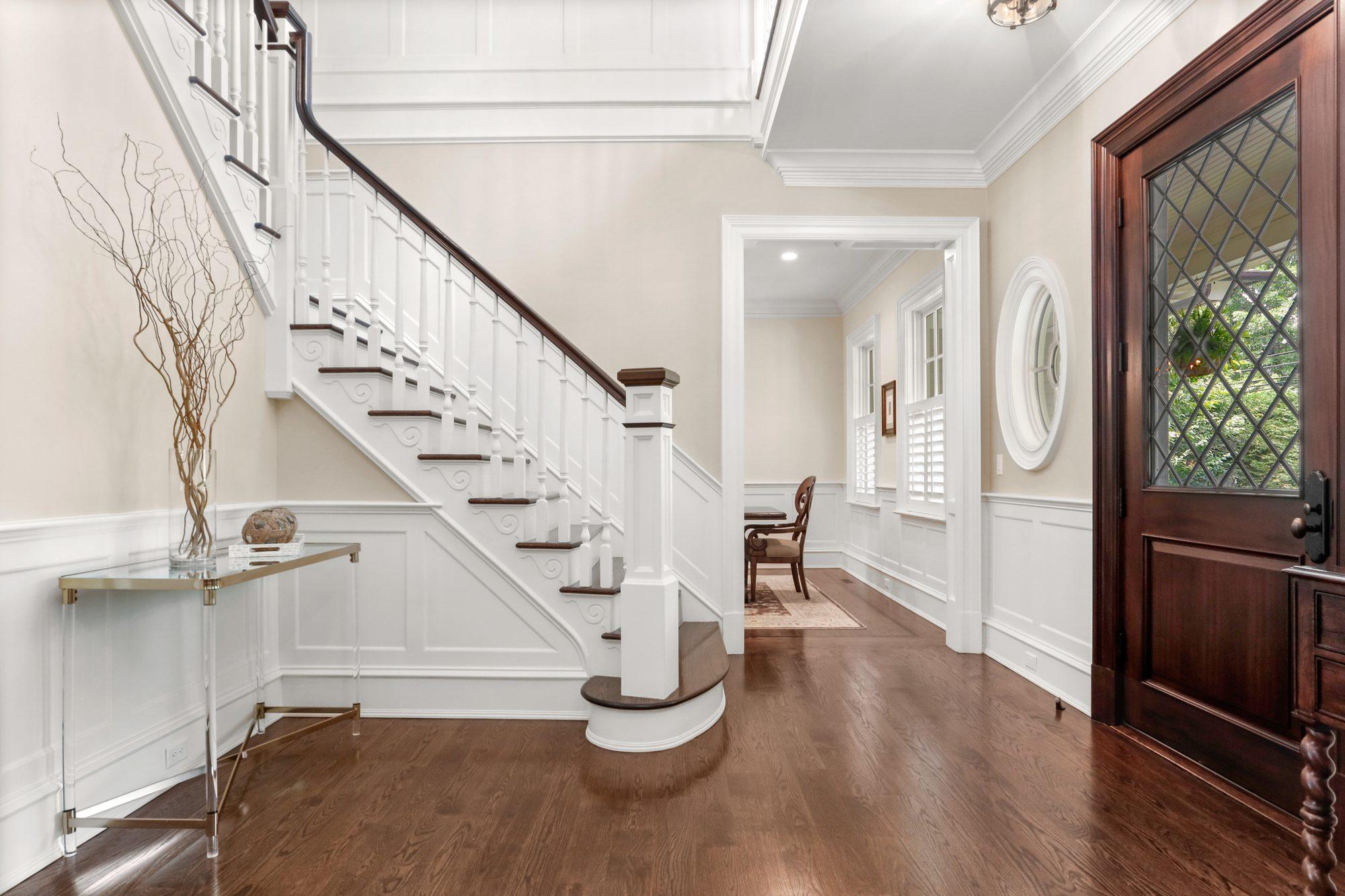 Foyer with medium brown hardwood floors and an eggshell finish.