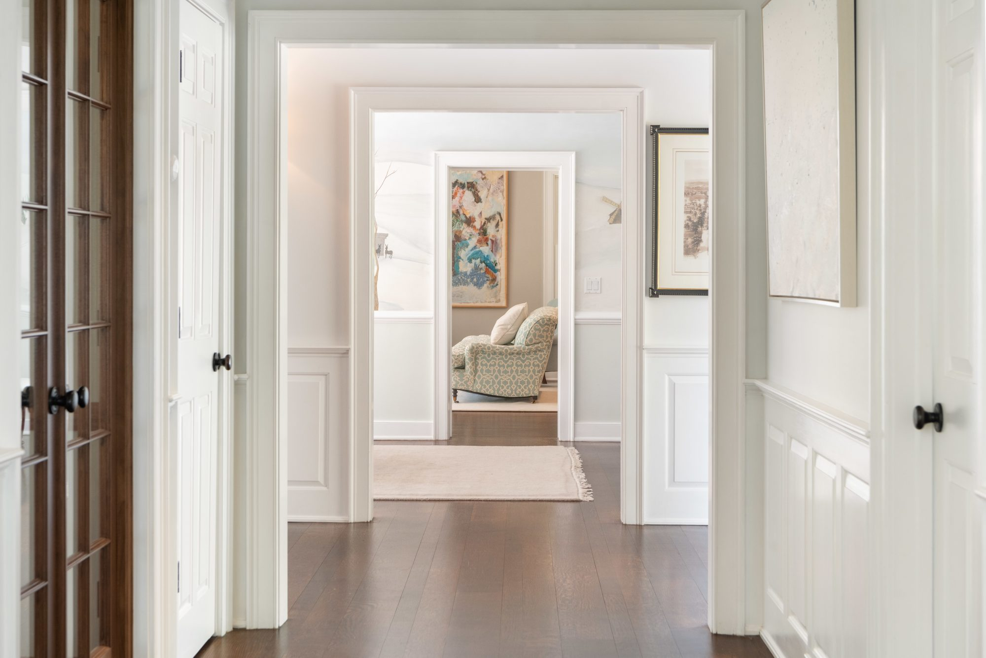 hallway with wainscoting and medium brown wood floors and an eggshell finish