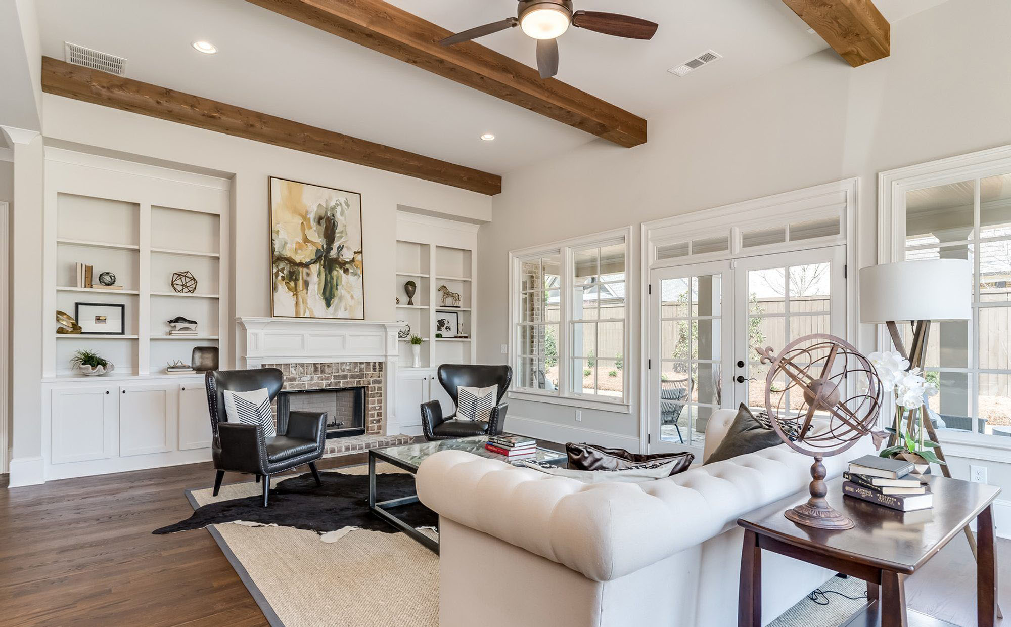 Custom home with hardwood floors and matching wood ceiling beams.